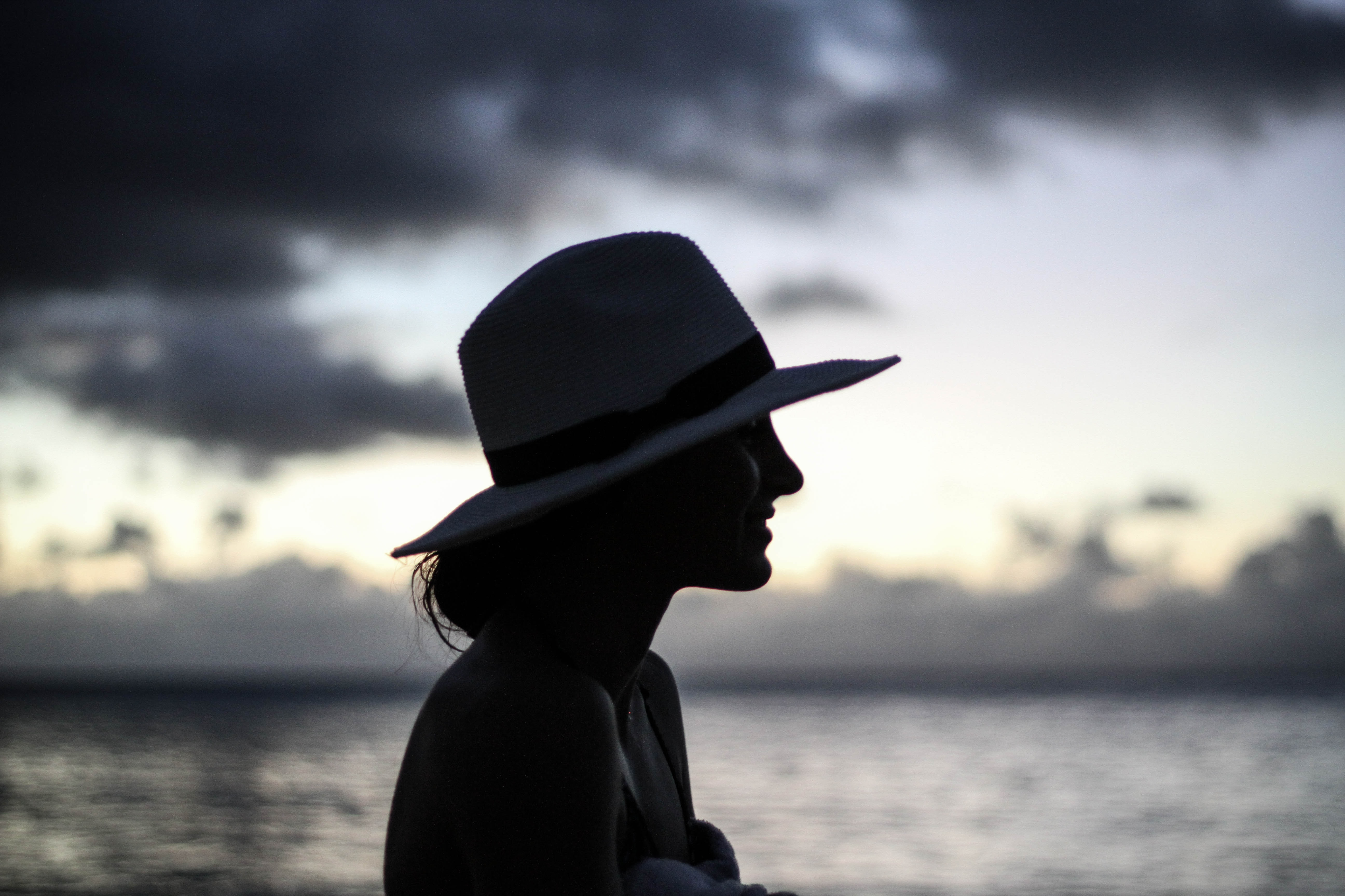 The silhouette of a woman wearing a hat during sunset at Waimea Bay