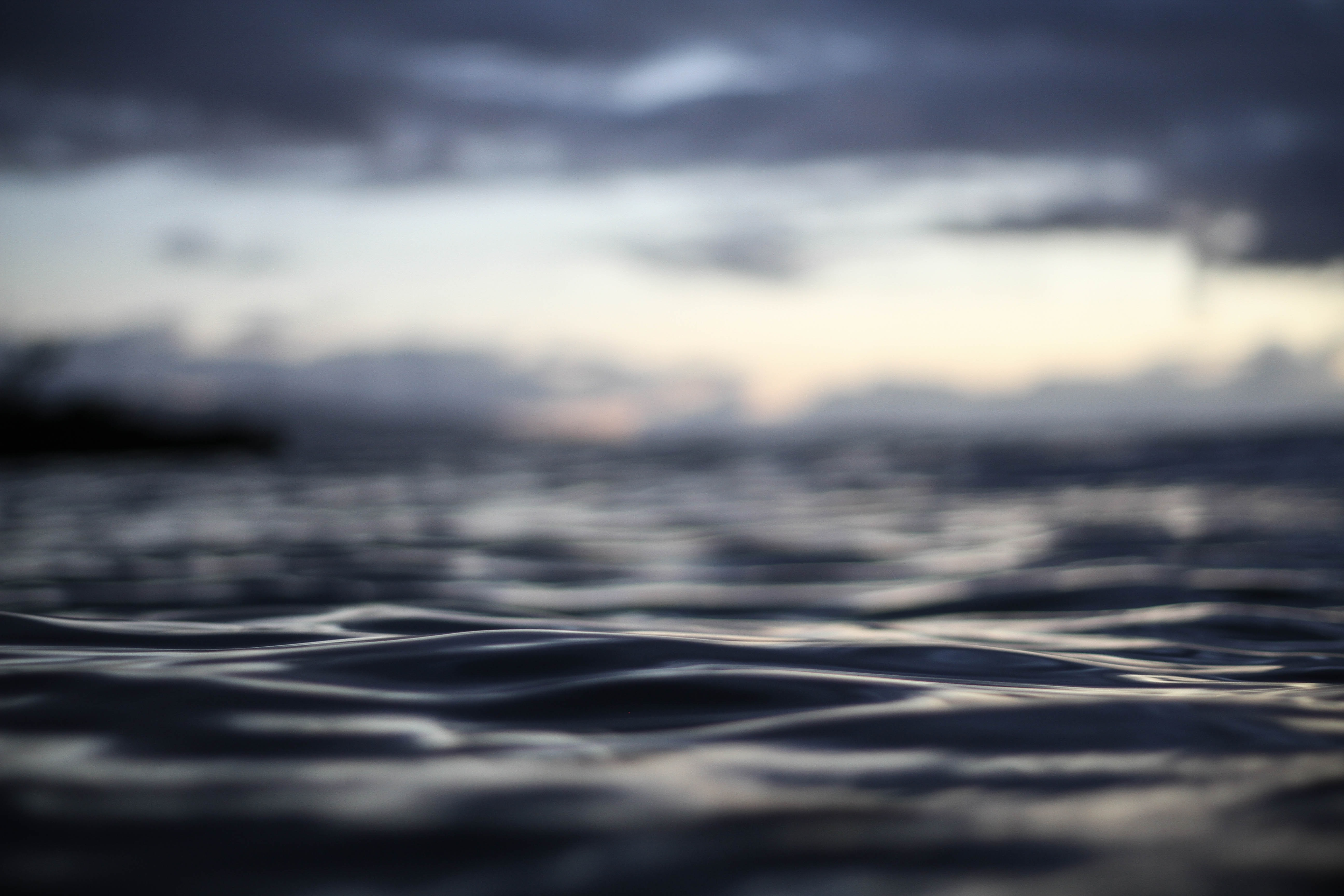 Close up of the dark ocean waters of Waimea Bay under a cloudy sunset