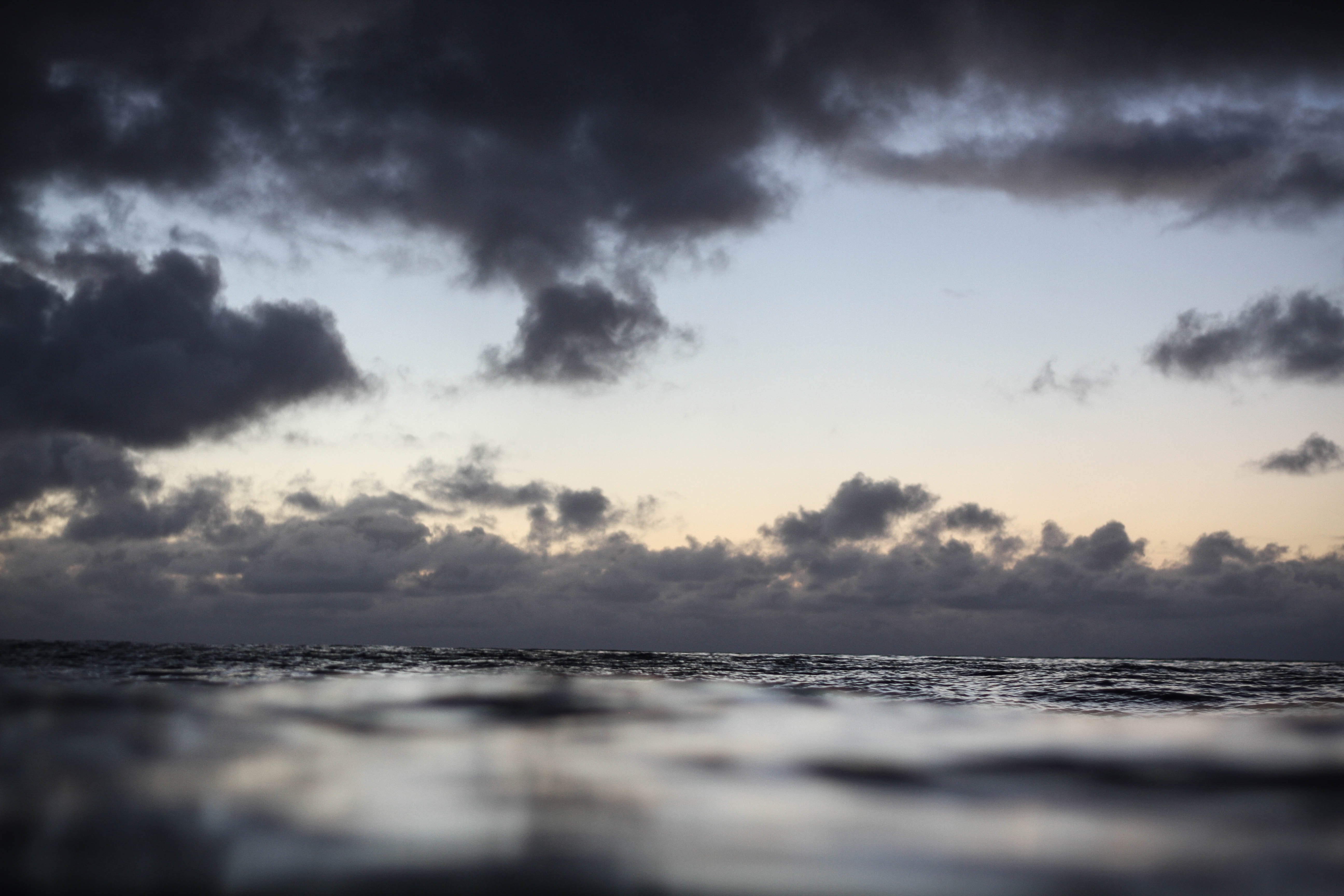 The view of a stormy horizon in the evening from the ocean surface in Waimea Bay