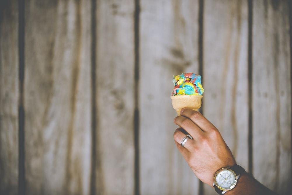 person holding multicolored ice cream