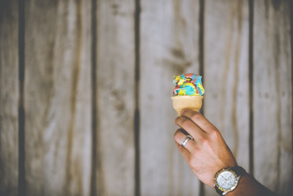 person holding multicolored ice cream
