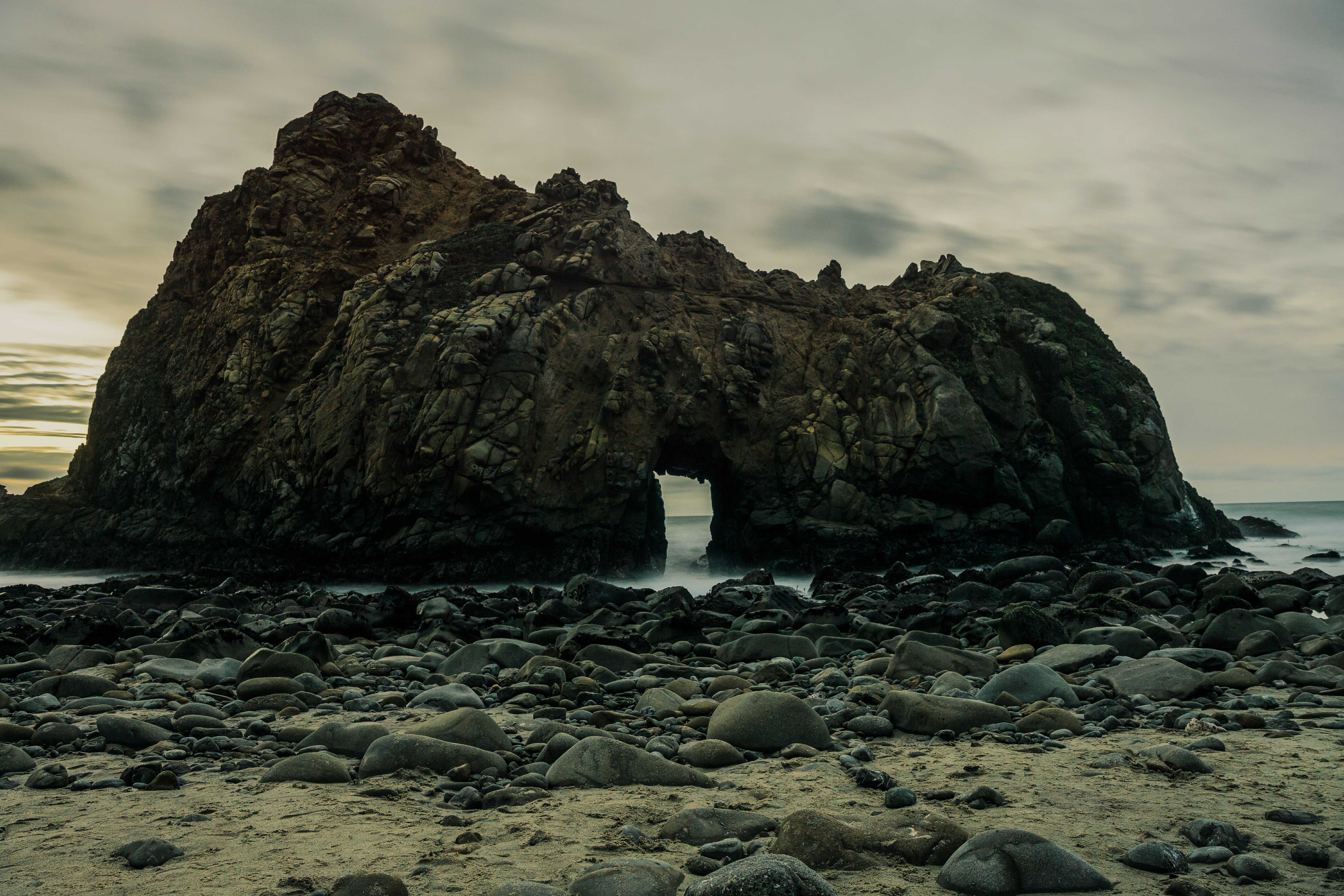 A rock formation with a tunnel on the beach.