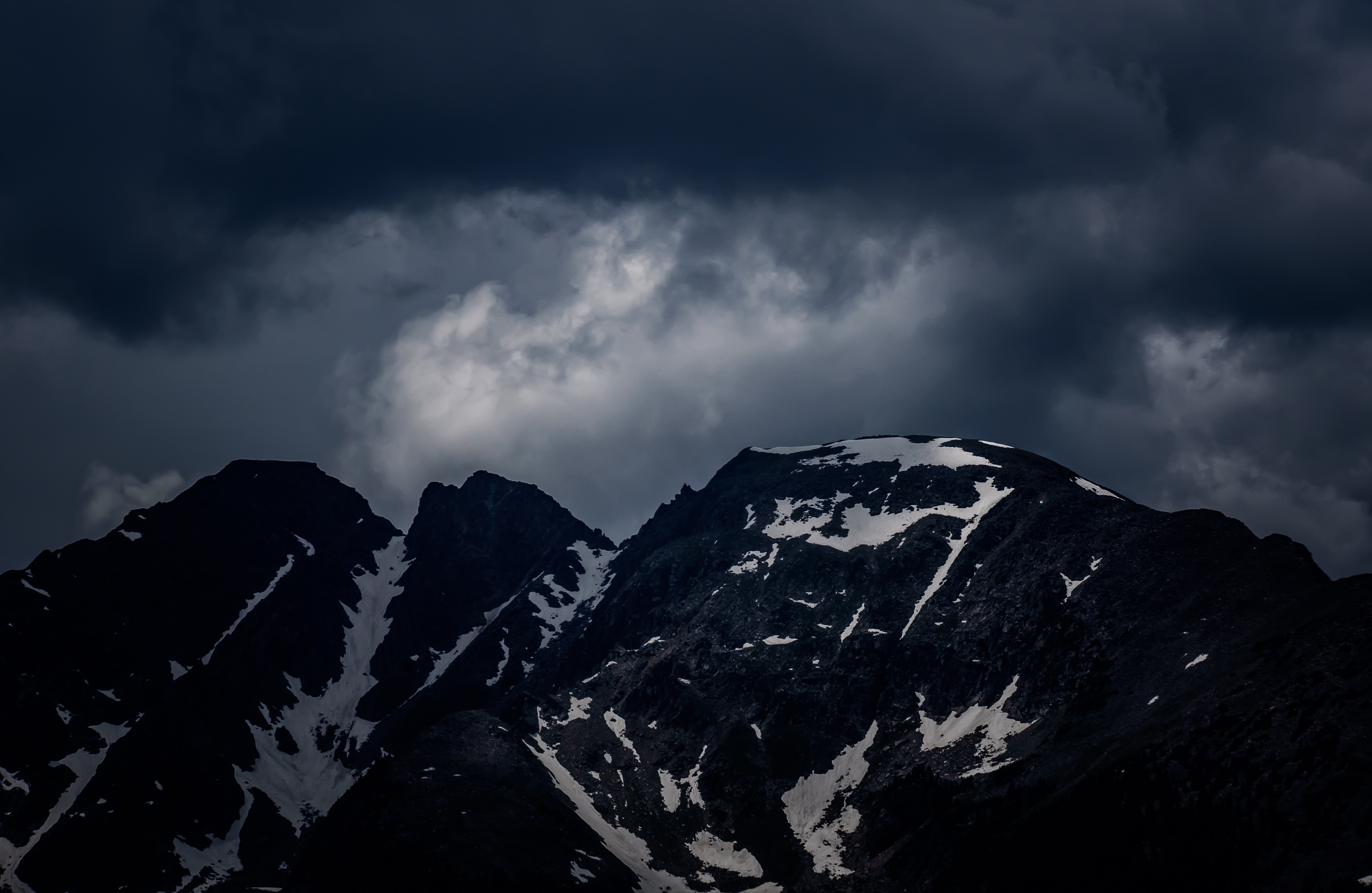 Dark storm clouds roll in over snowy mountains in Silverthorne