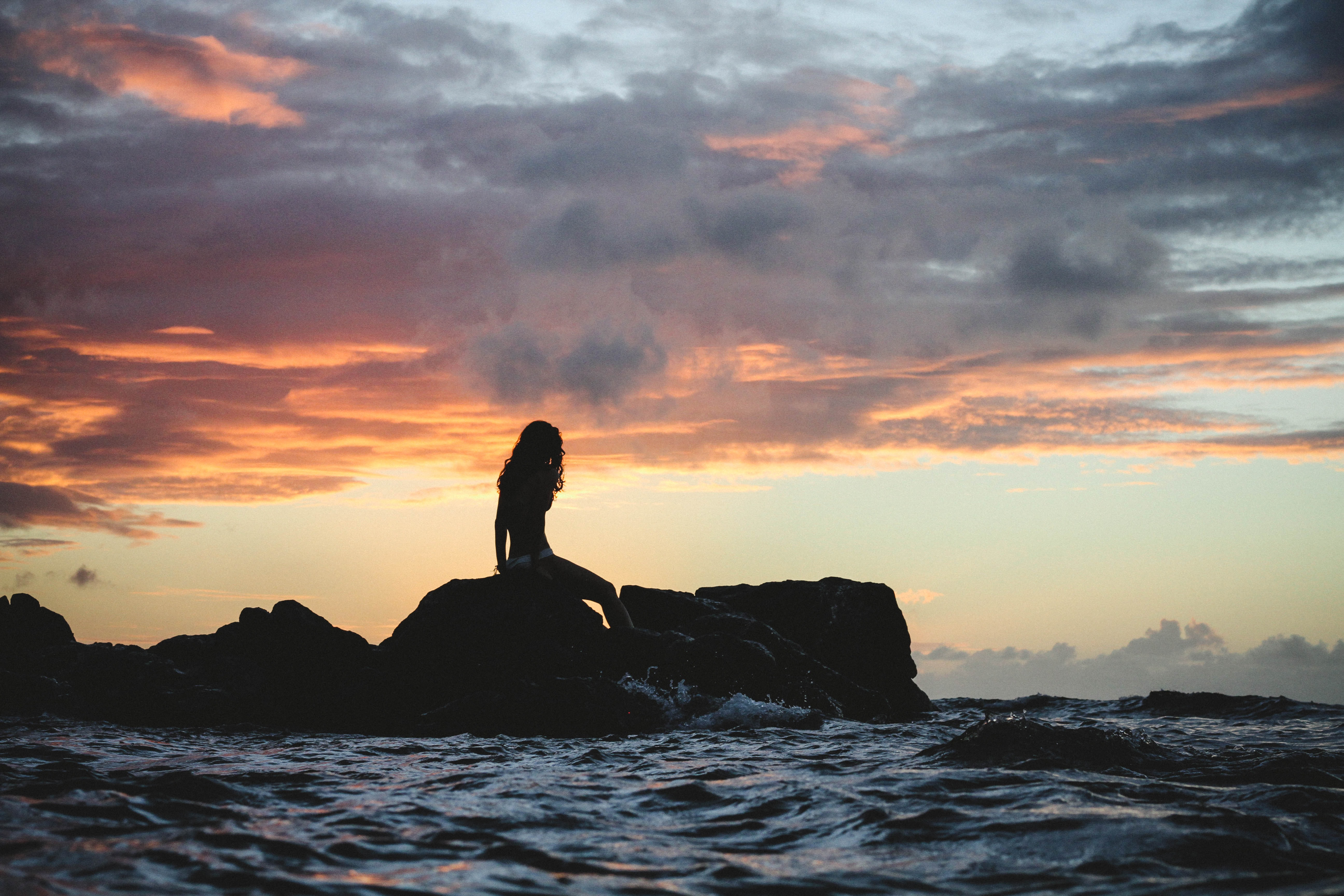 A sunset casts a silhouette of a Hawaiian mermaid sitting atop of rocks above the sea