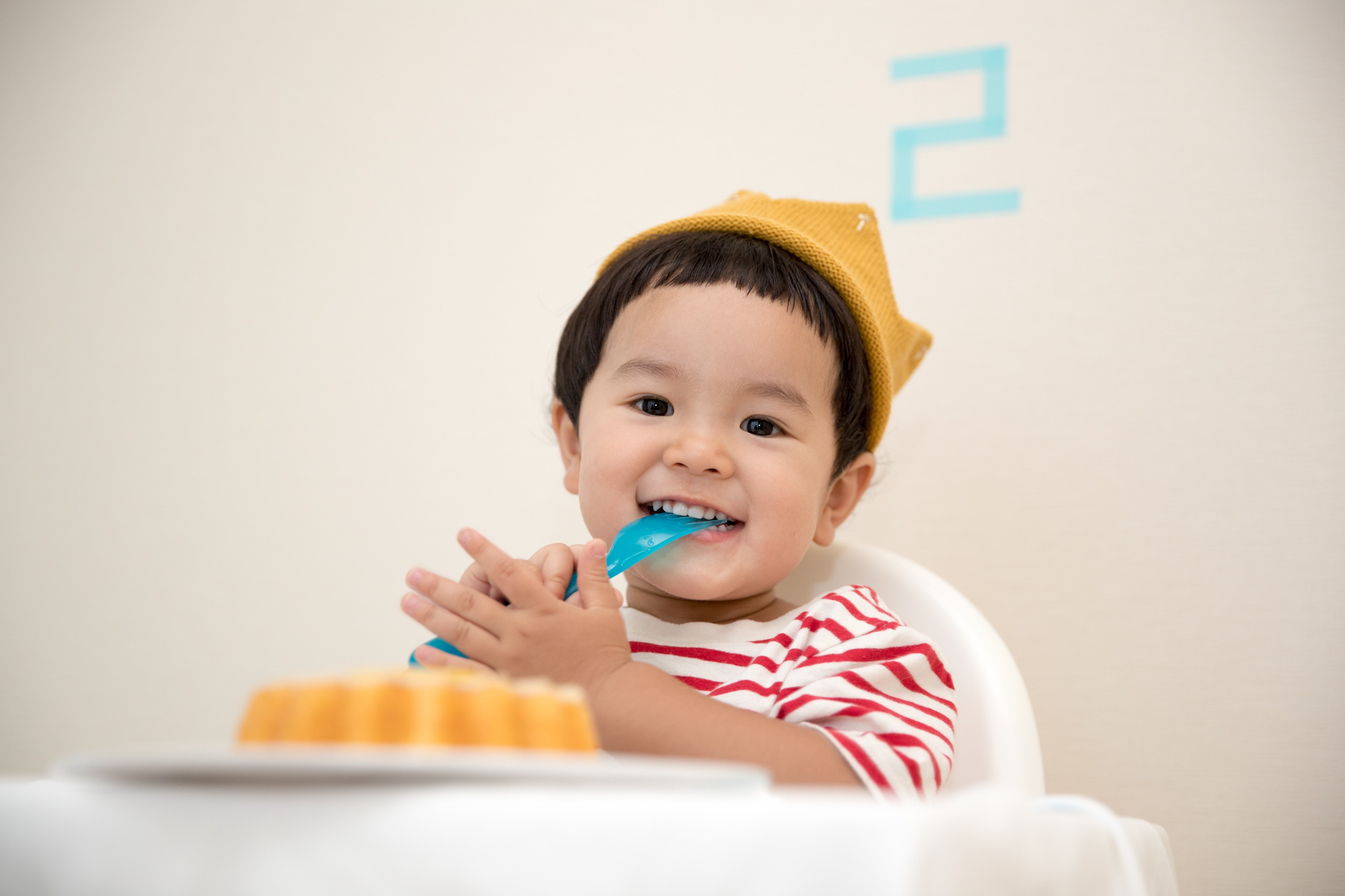 A little boy at his birthday party eating cake