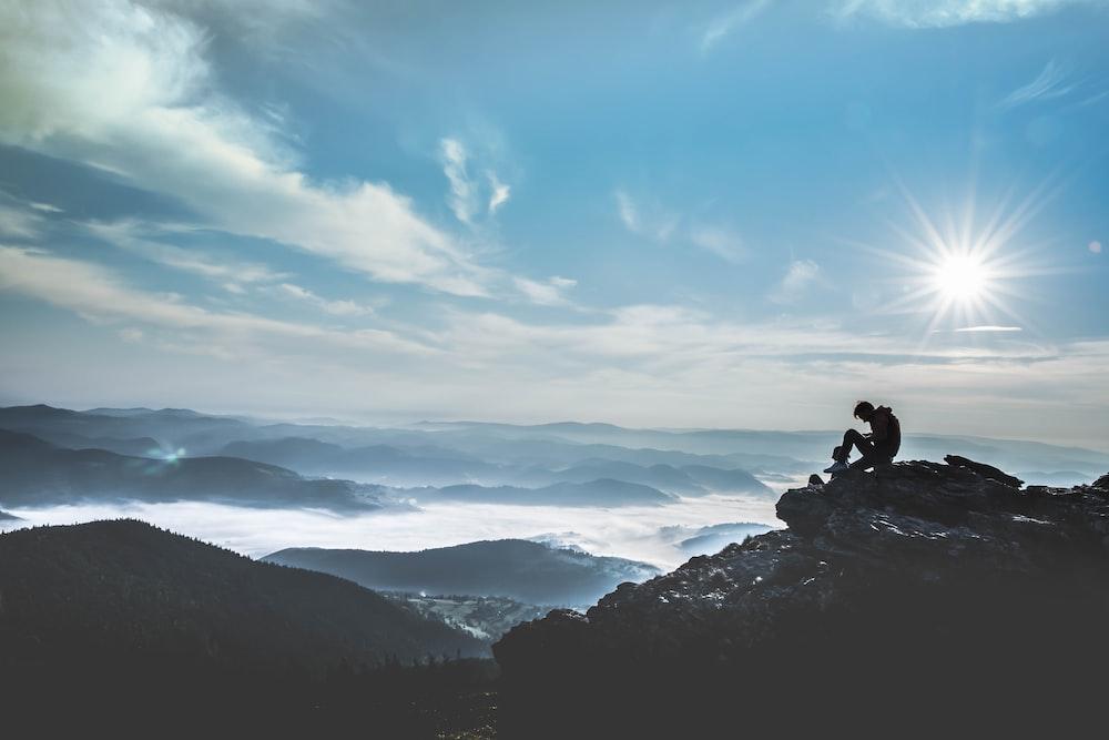 man sitting on rock during daytime