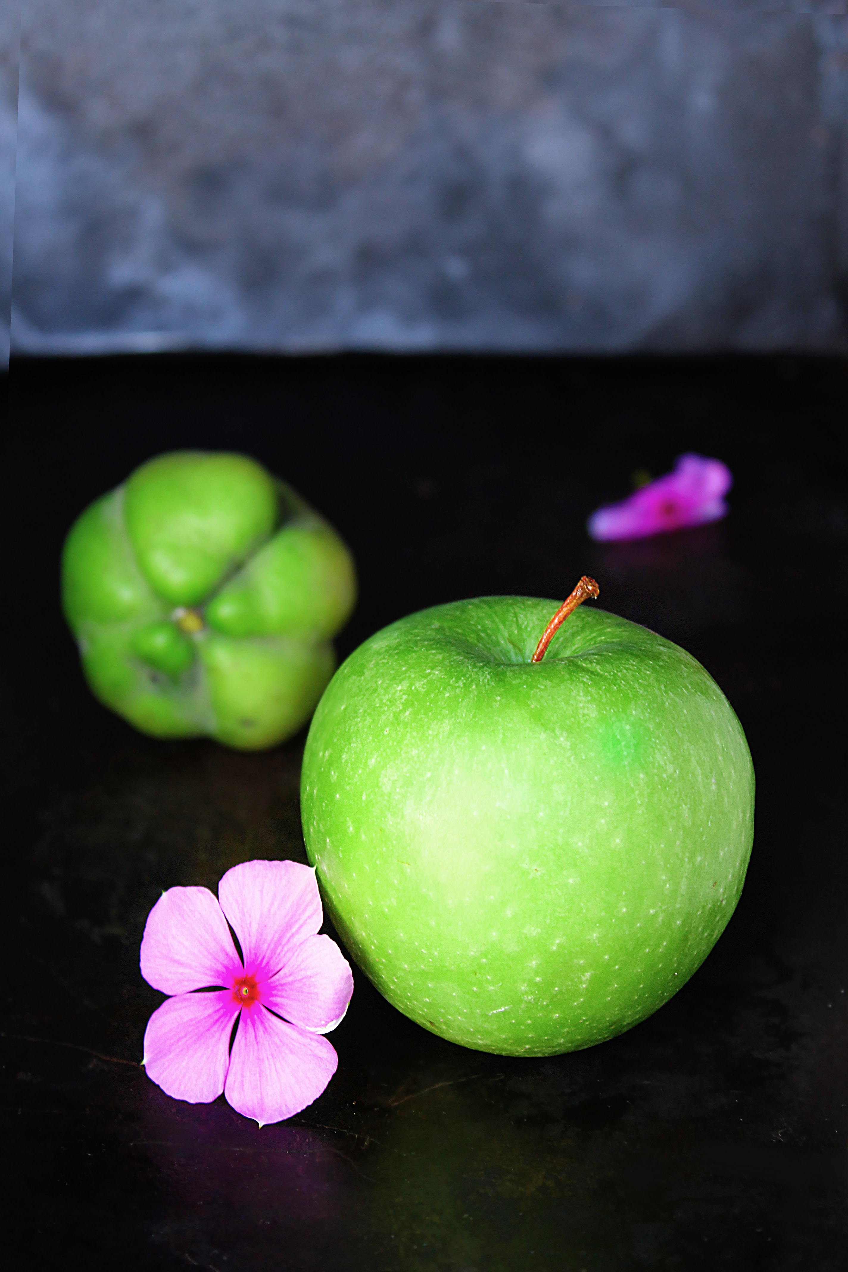 Fresh green granny smith apple next to purple flowers and a green fruit