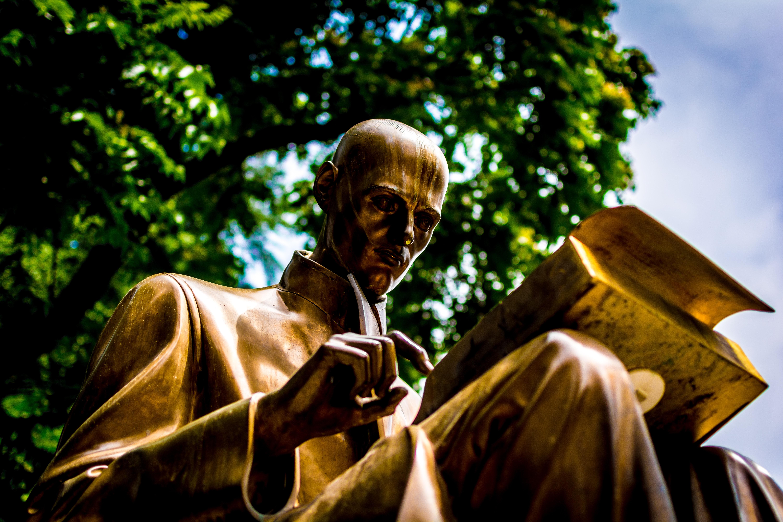 bronze man reading book statue