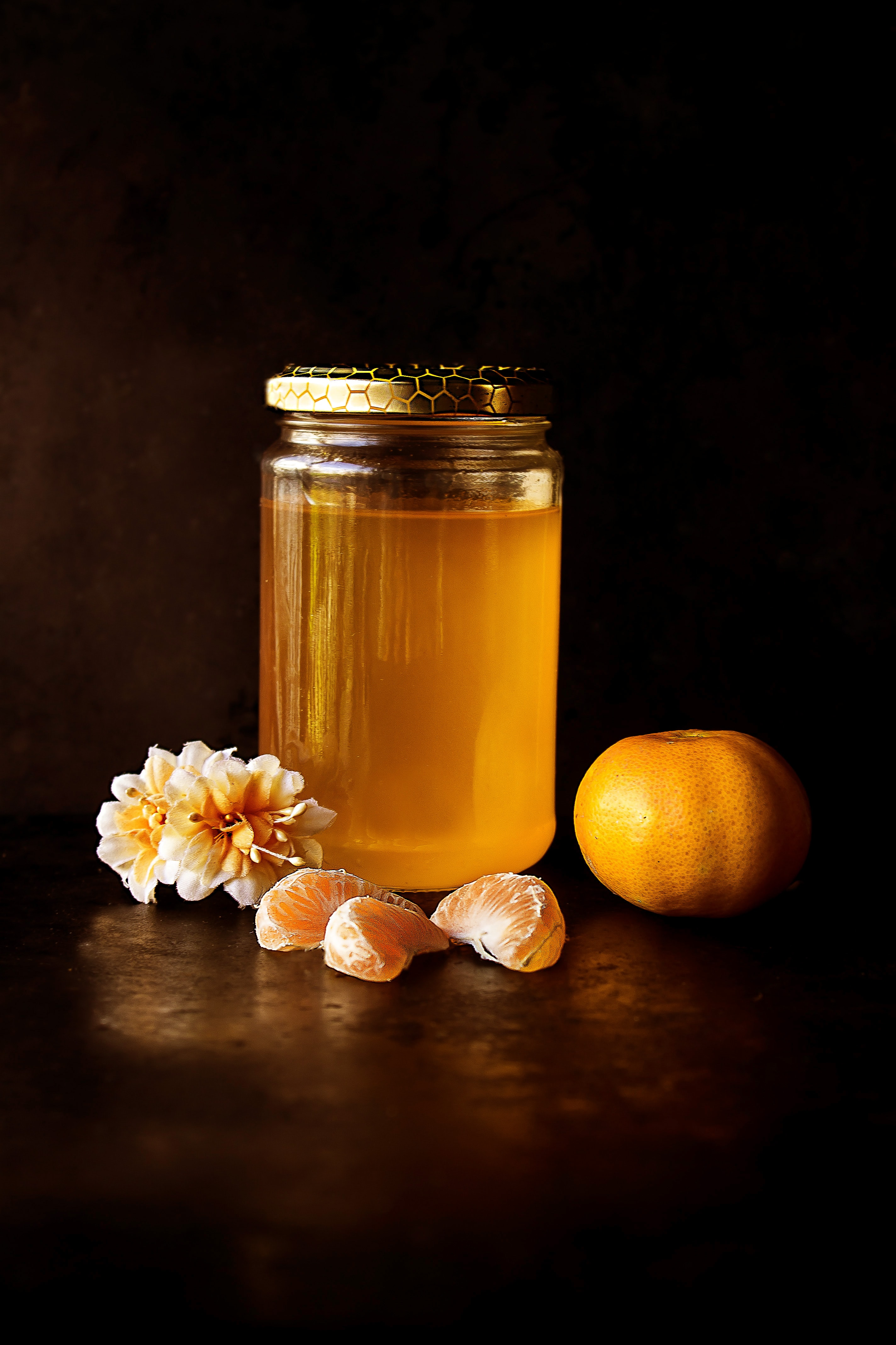 Homemade jar of honey, orange clementine slices, and a flower blossom