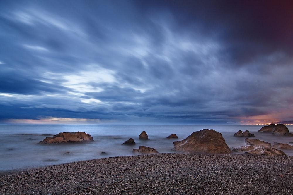 rocks at seashore under clouds