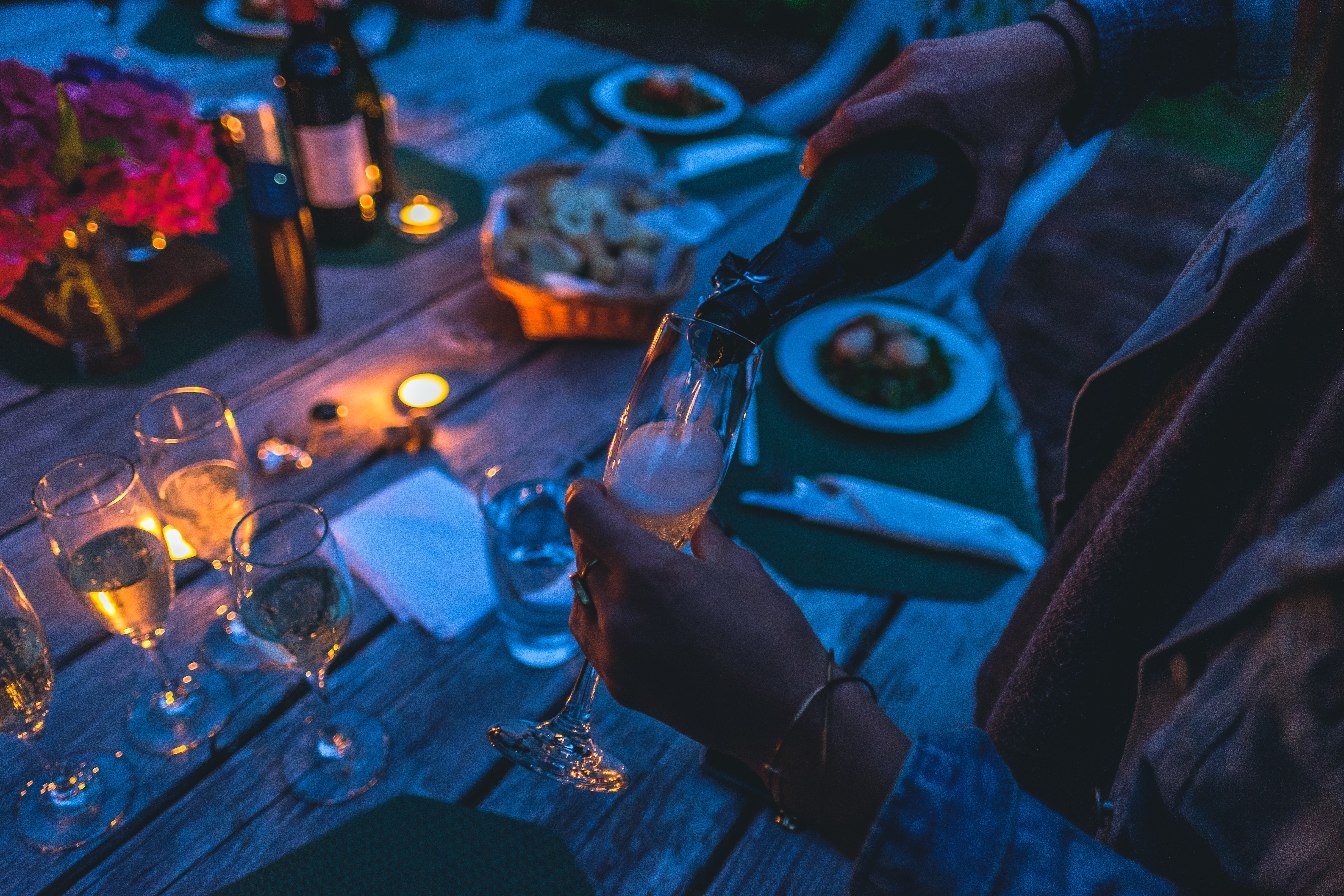A person pouring champagne into a tall glass at a large outdoor table in the evening