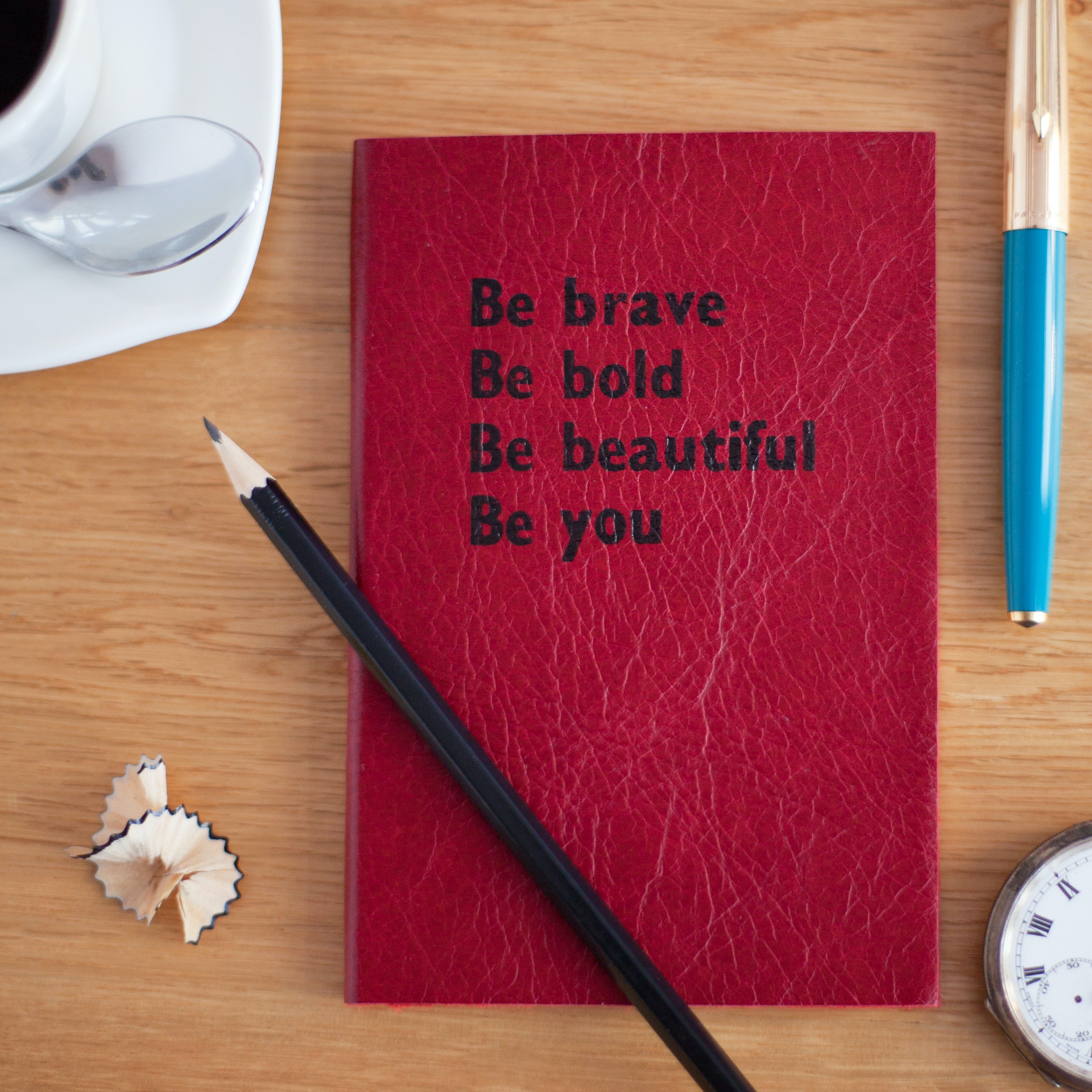 "A red book with black titling that says ""Be brave Be bold Be beautiful Be you."""