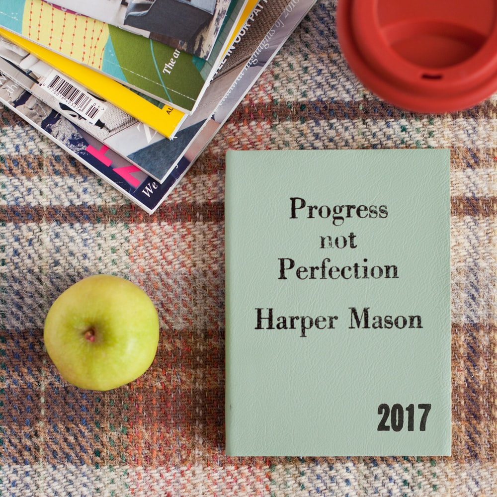 """A book that says """"Progress not Perfection,"""" written by Harper Mason (2017), placed next to an apple and other books."""