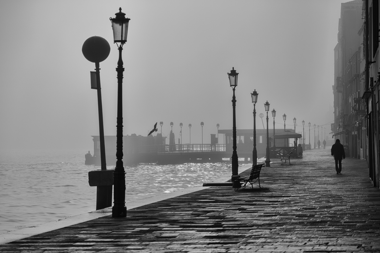 Walking alone on the pier near the water in Metropolitan City of Venice