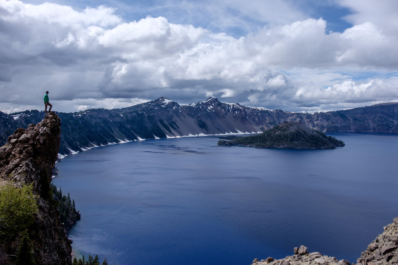 man standing on lake cliff near mountain alps