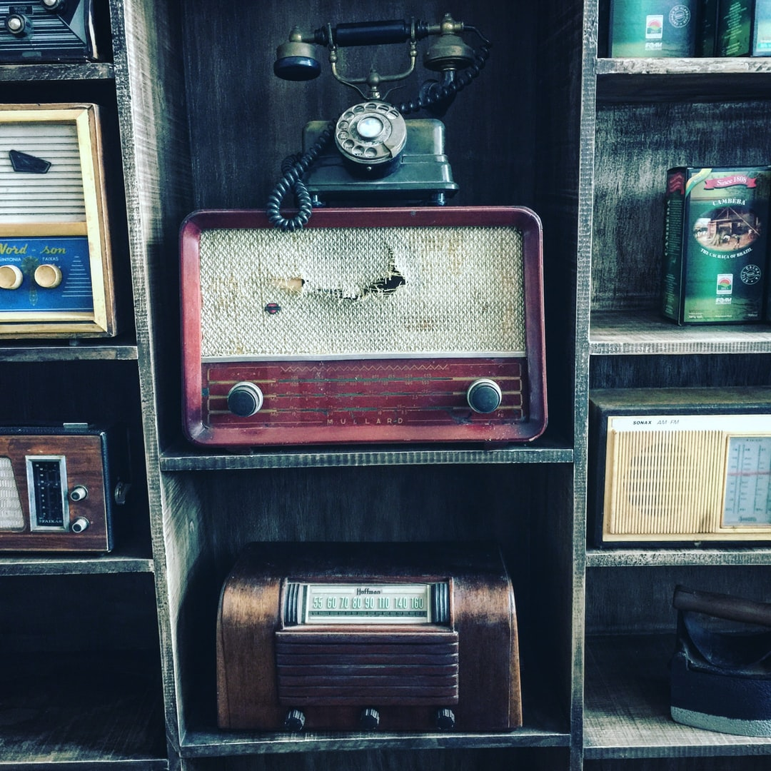 A collection of old radios and an old telephone on shelves