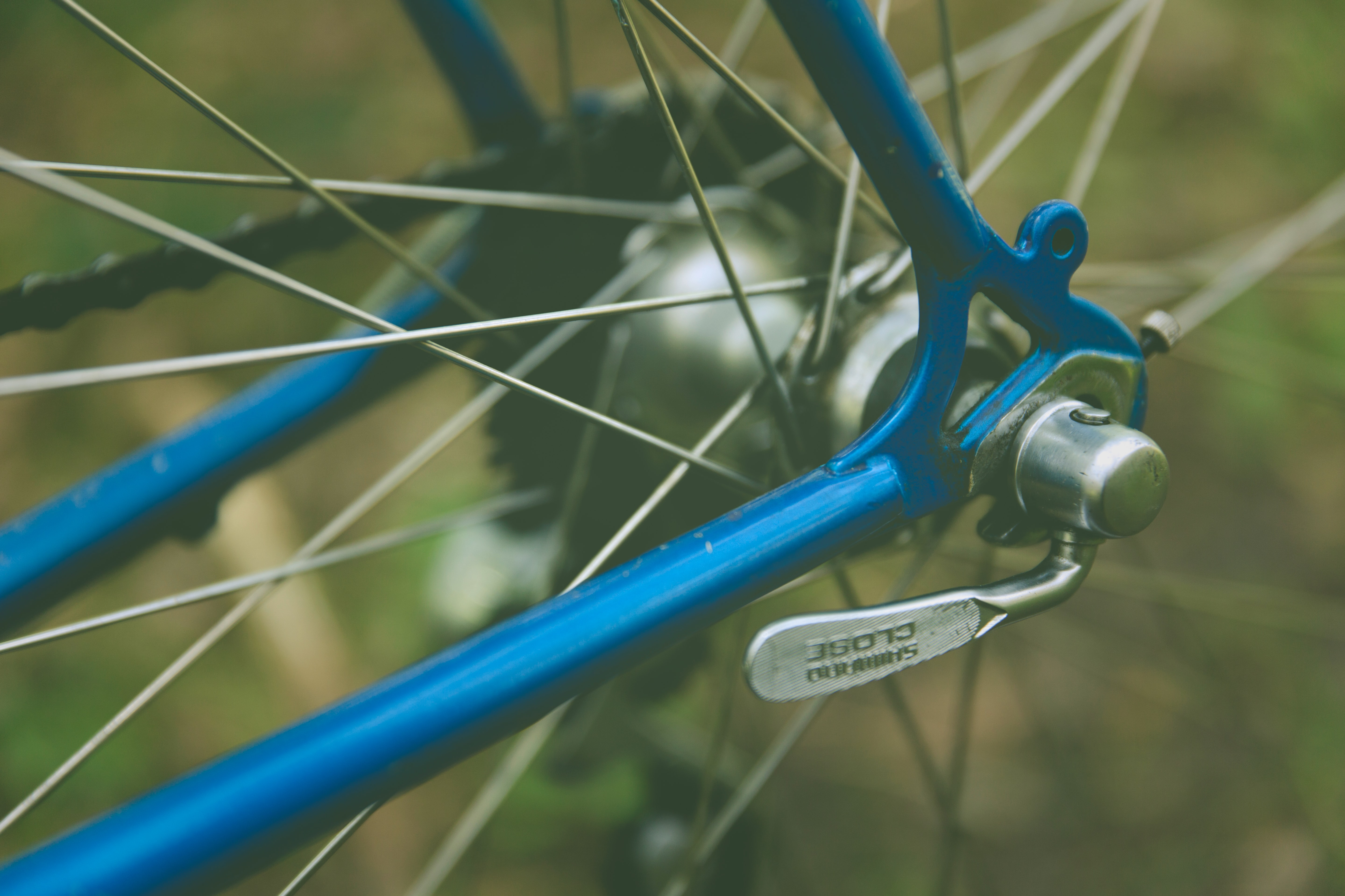 Spokes and framing details on a blue bicycle