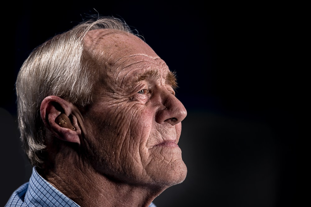 Old man with wrinkle face and gray hair looking out and using a hearing aid.