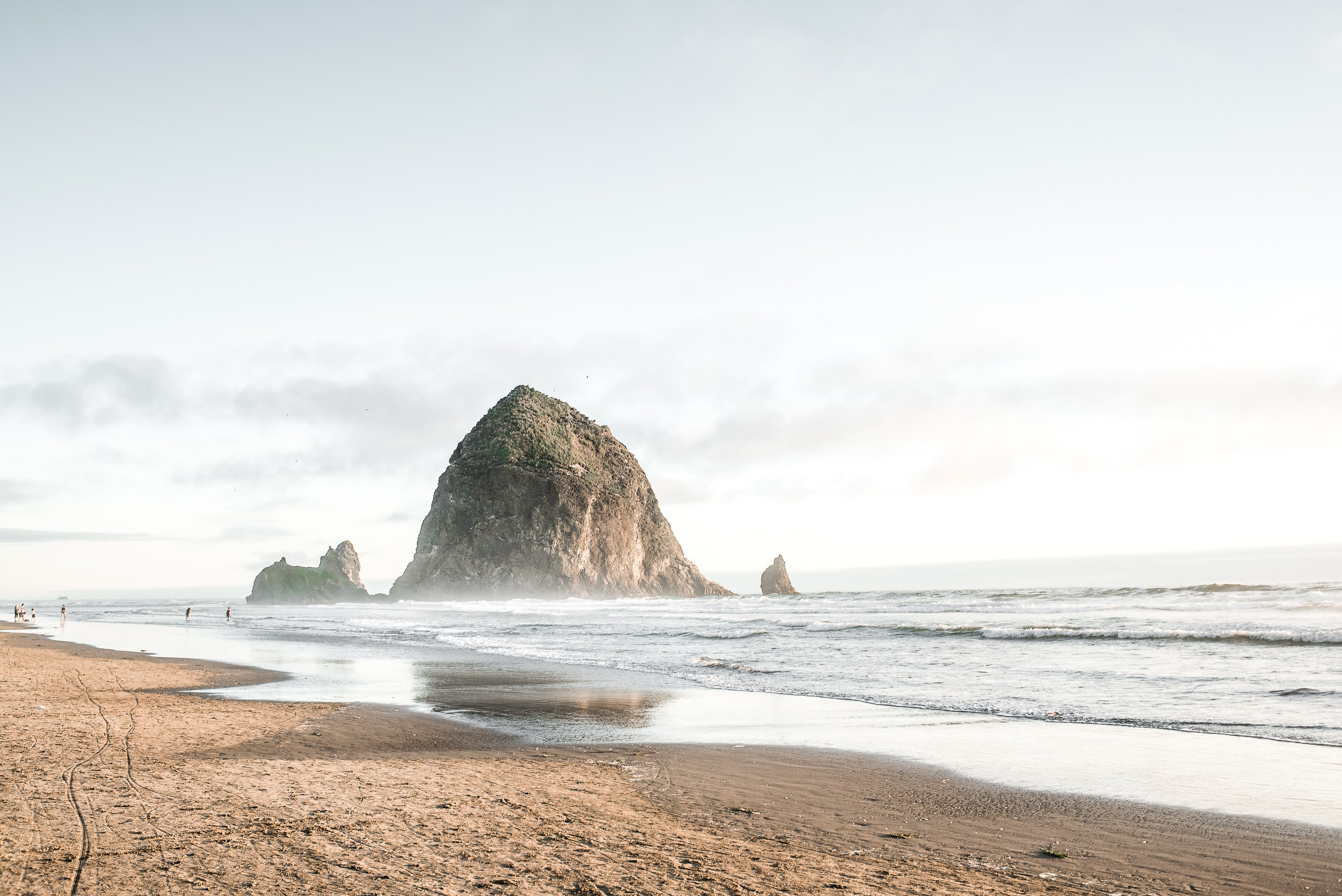 View from the sand beach on the large mountain rock in the ocean at Cannon Beach, Oregon.