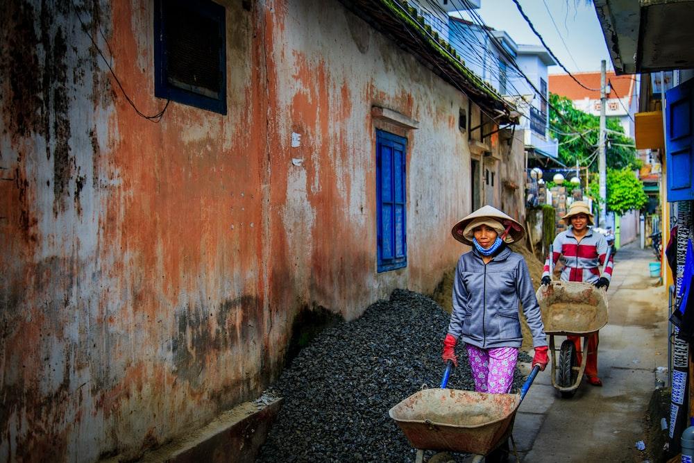 two women walking beside orange house