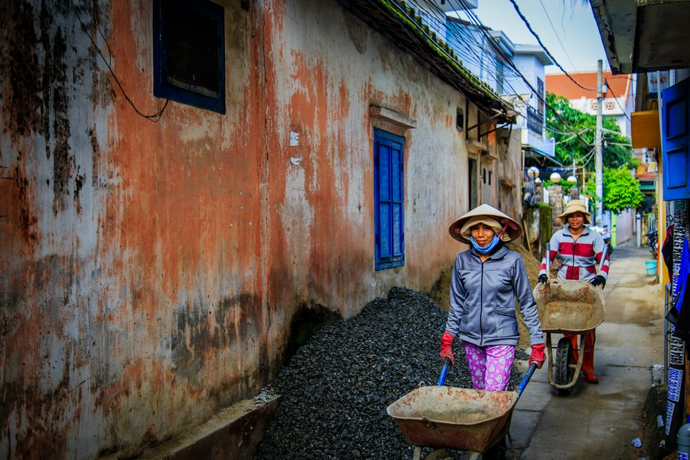 two women walking beside orange house