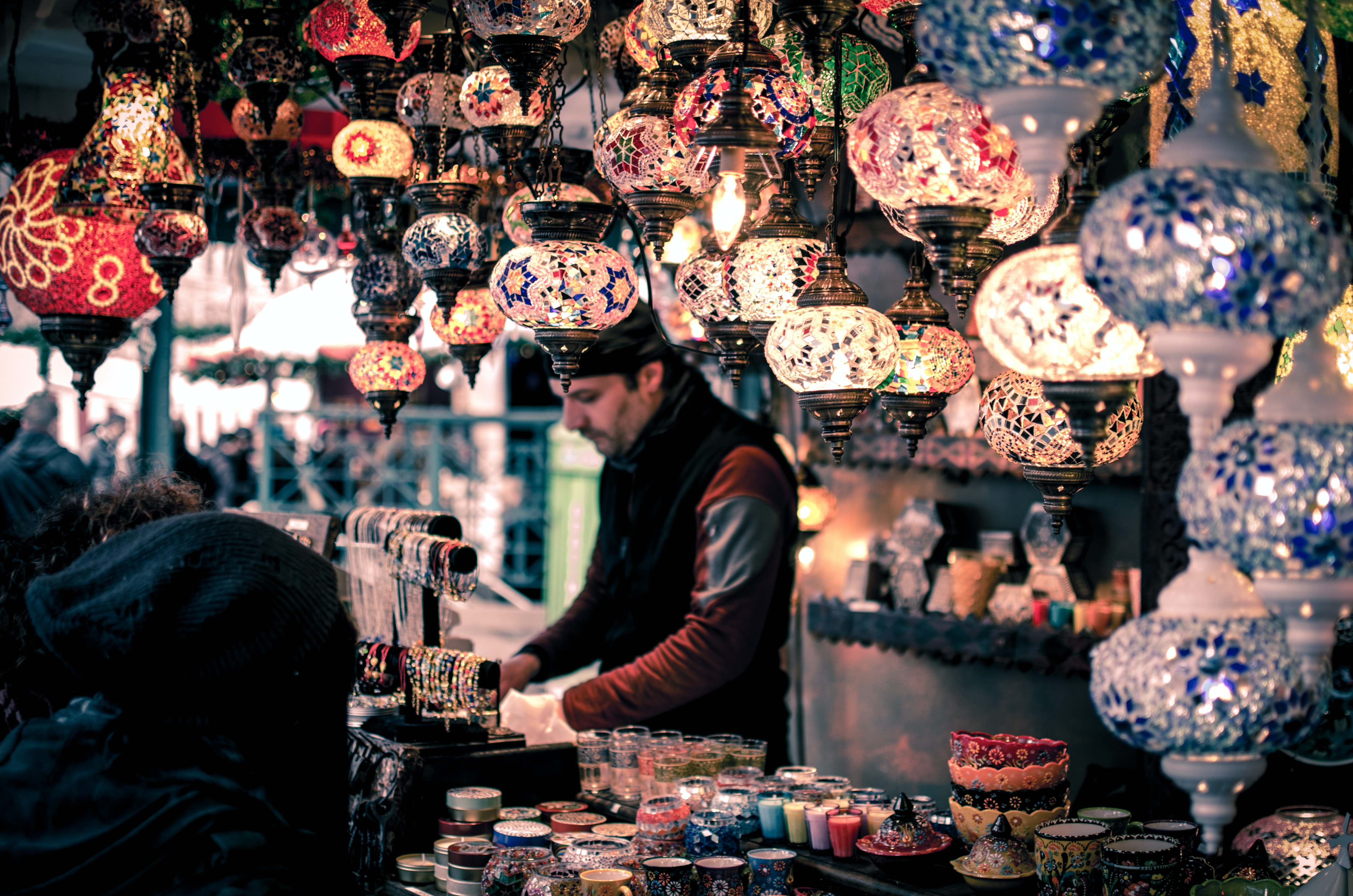 Colorful lanterns hanging above a street market stall with various decorative items