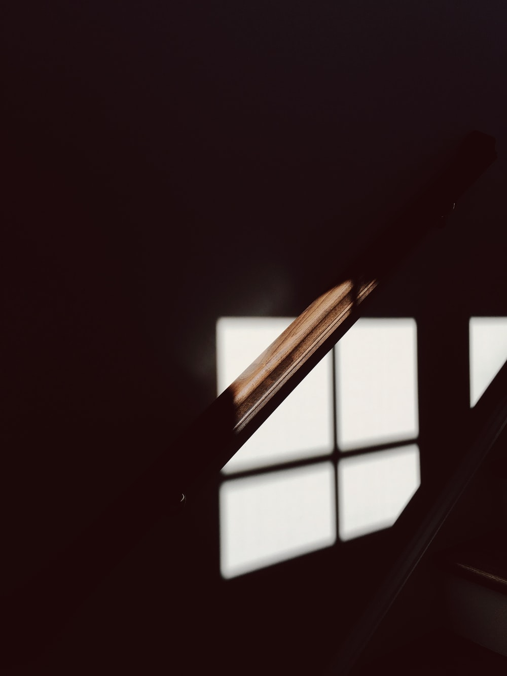A dim shot of a wooden bannister illuminated by faint light from the window