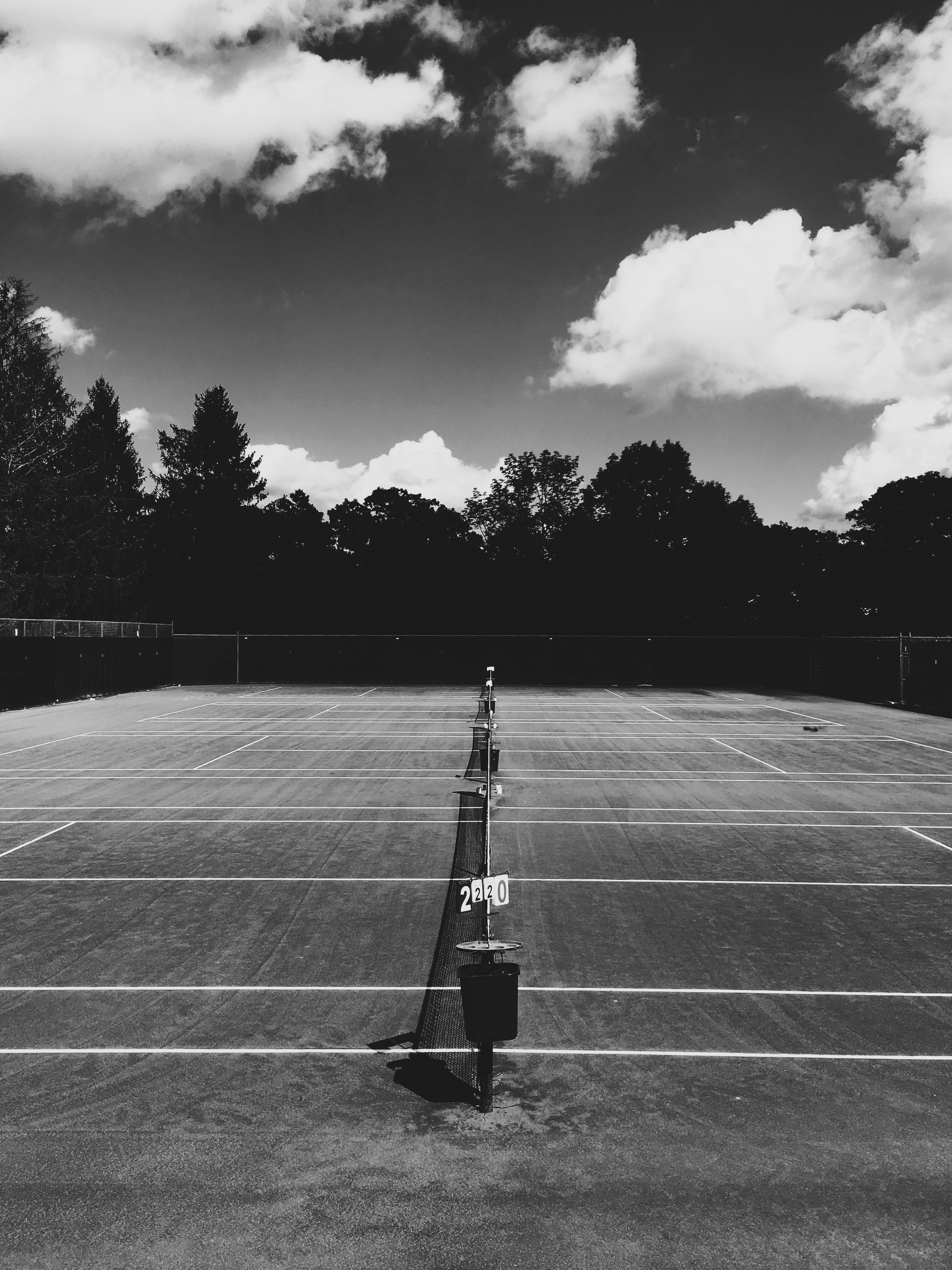 A look down the middle of a tennis net with a darkened background on a partially cloudy day.