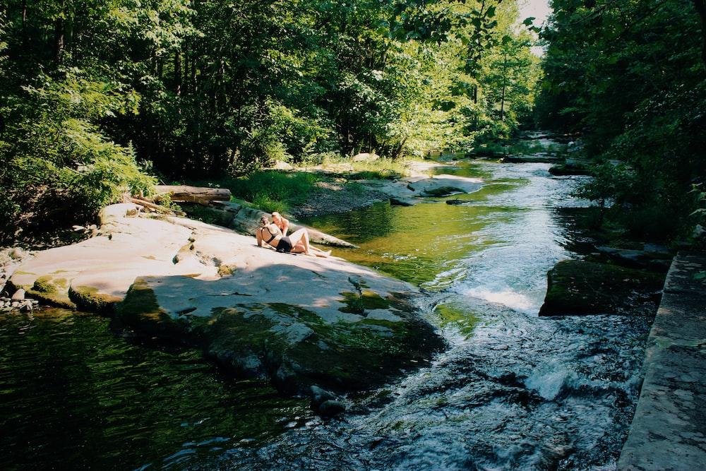 two women sitting on rock beside river