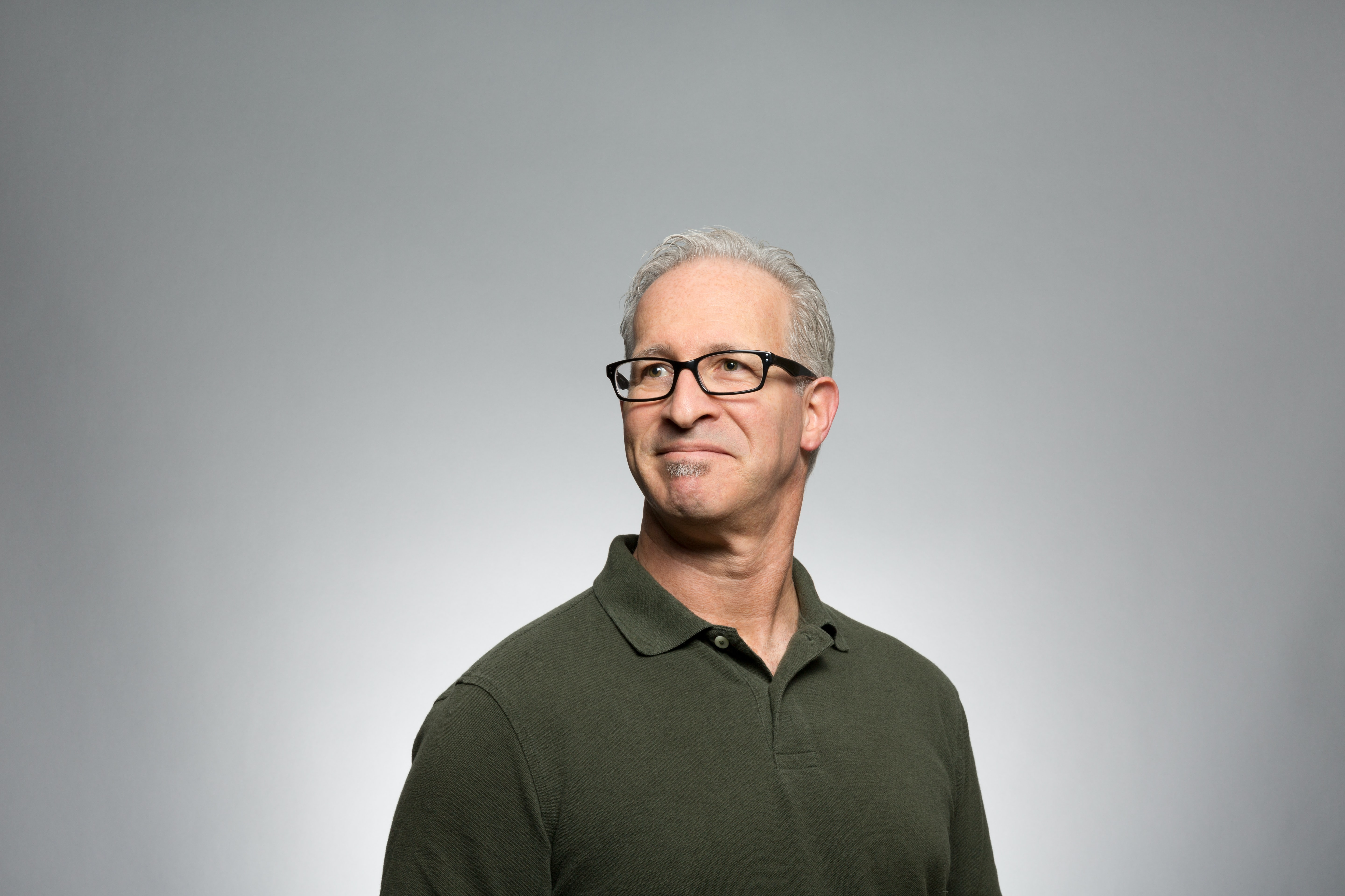 A smiling gray-haired man in glasses and a green polo shirt