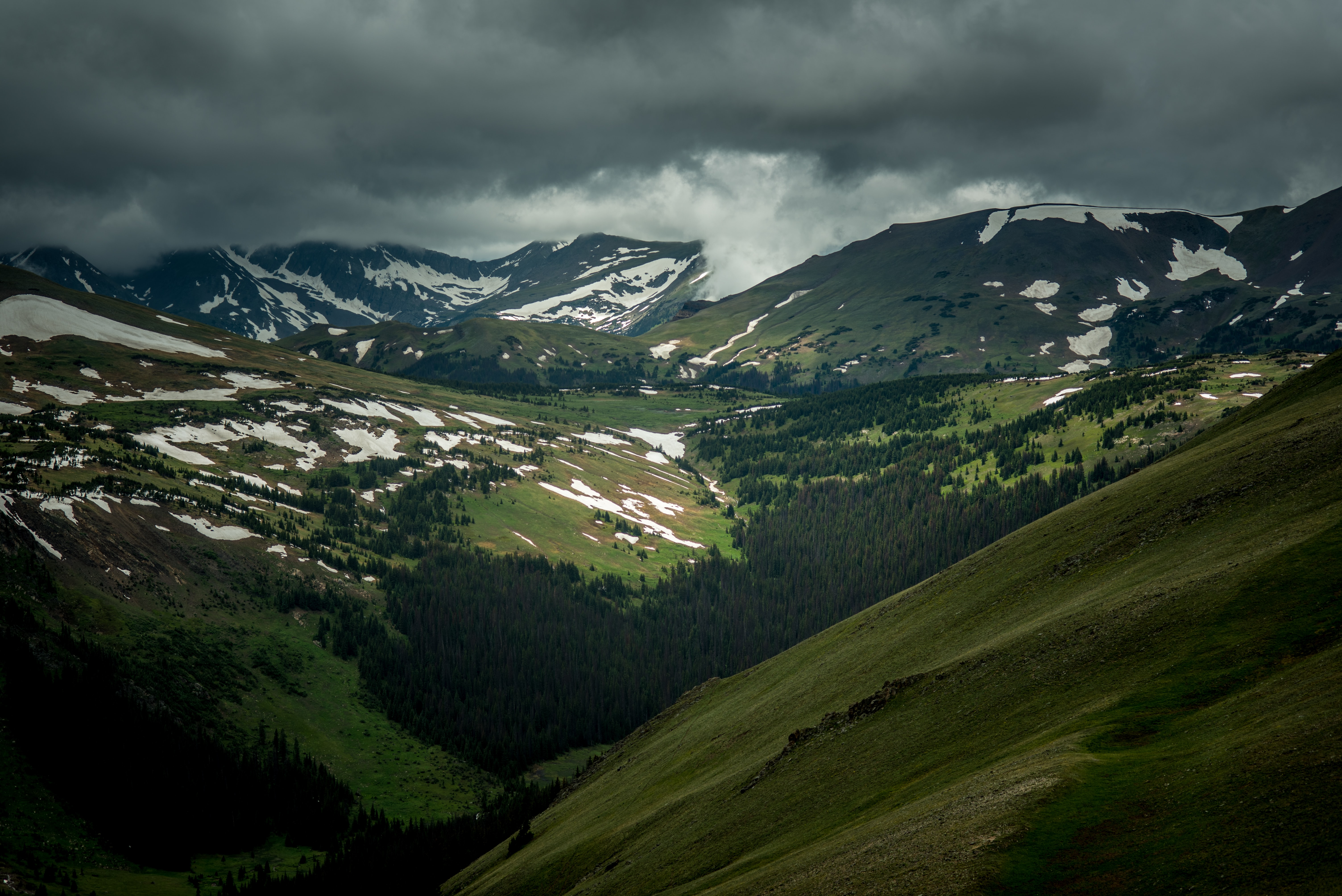 Patches of snow in a wooded mountain valley on a cloudy day
