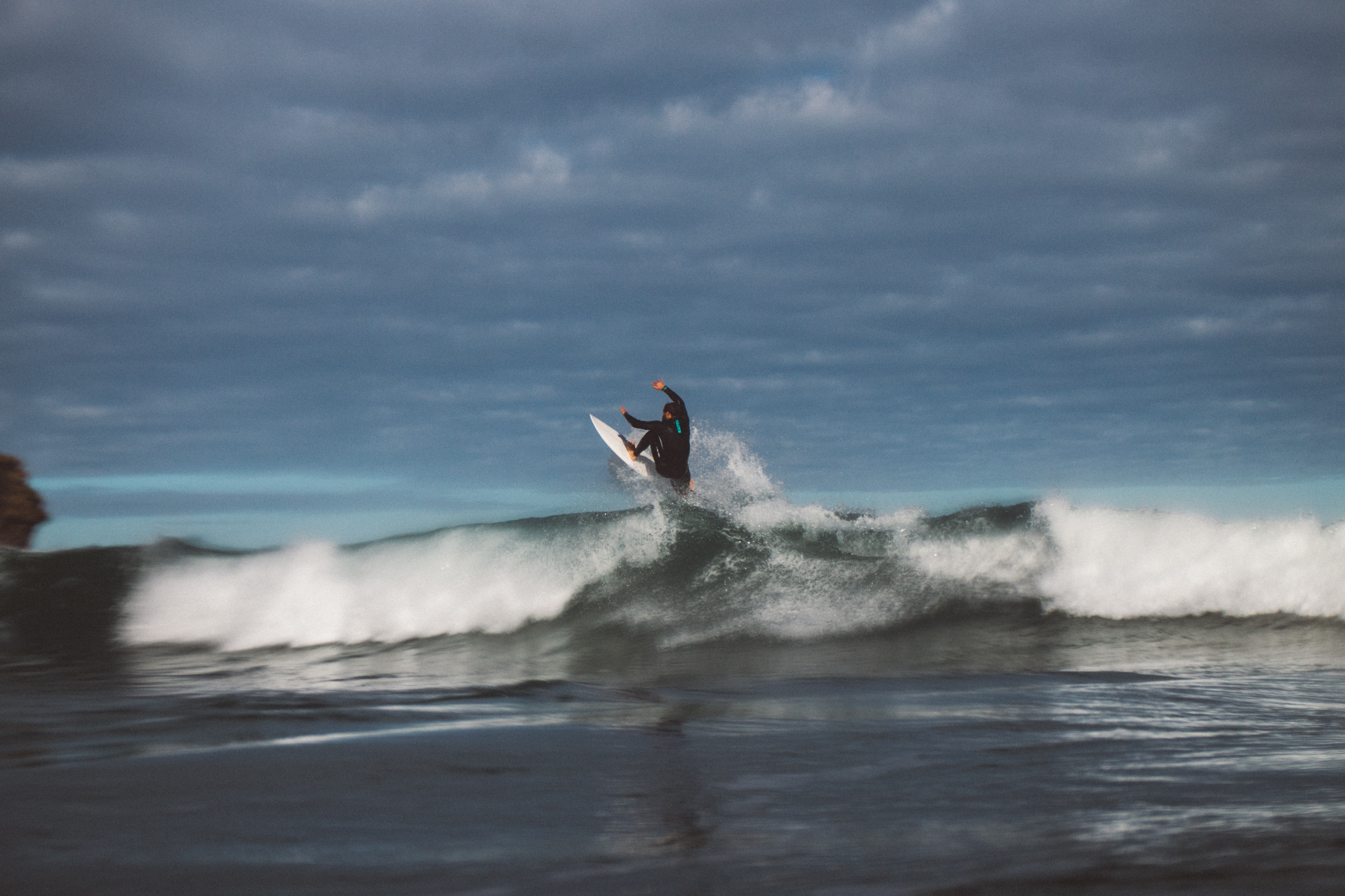 A man riding a wave with a surfboard in Piha, New Zealand