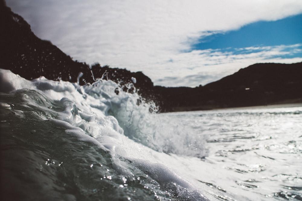 seawaves near mountain at daytime