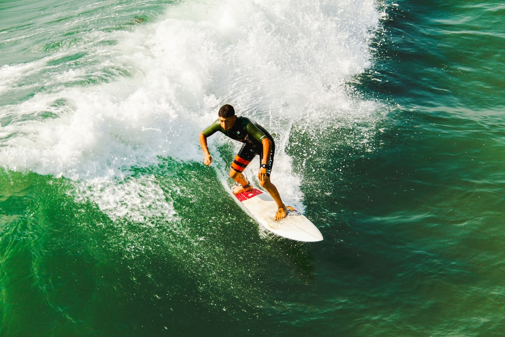 man on surfboard surfing against waves