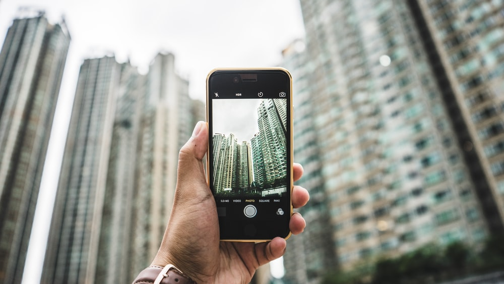 person using smartphone taking picture of building