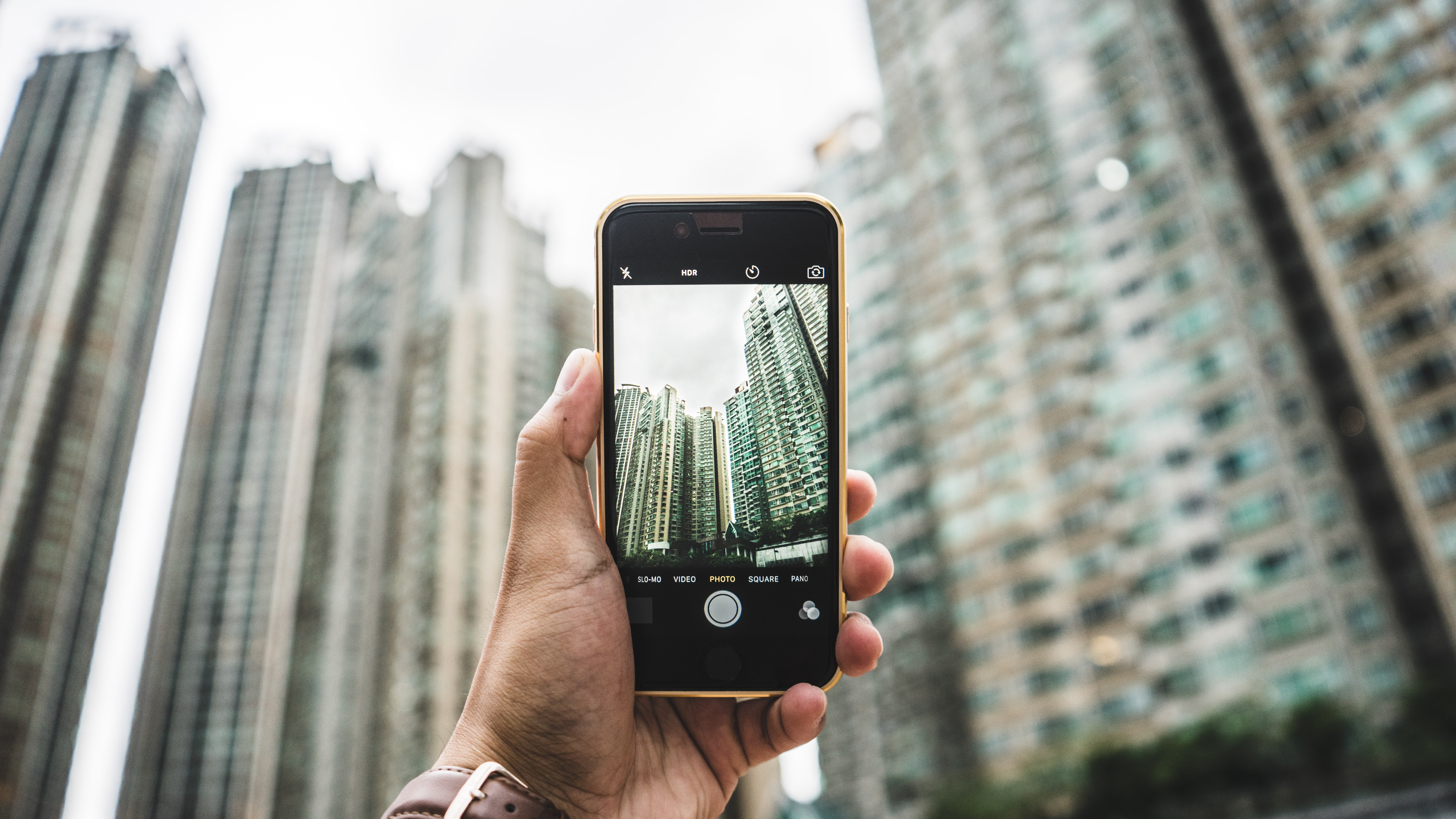 A person photographing skyscrapers in Hong Kong with an iPhone