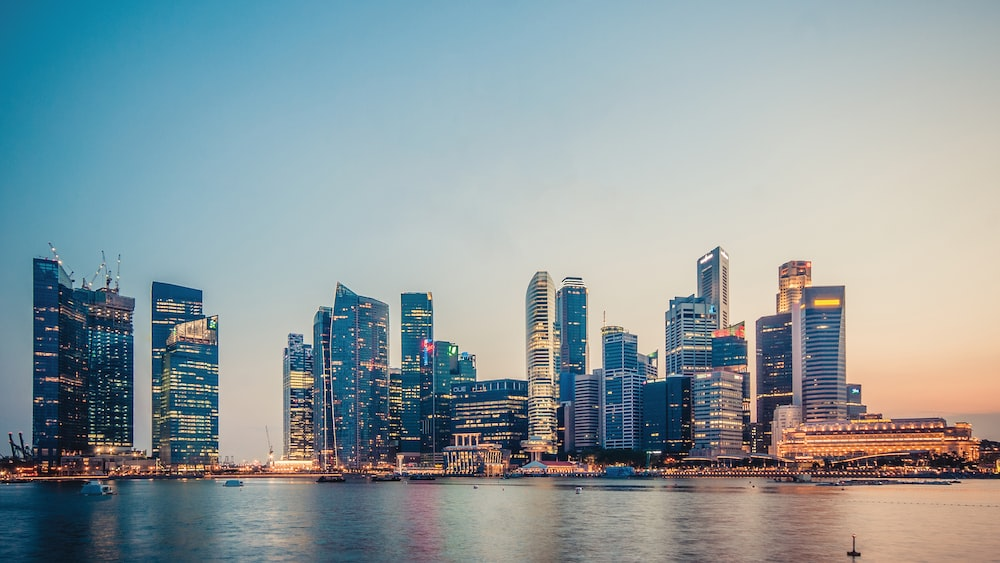 View of Marina Bay skyline and shores from the water during sunset