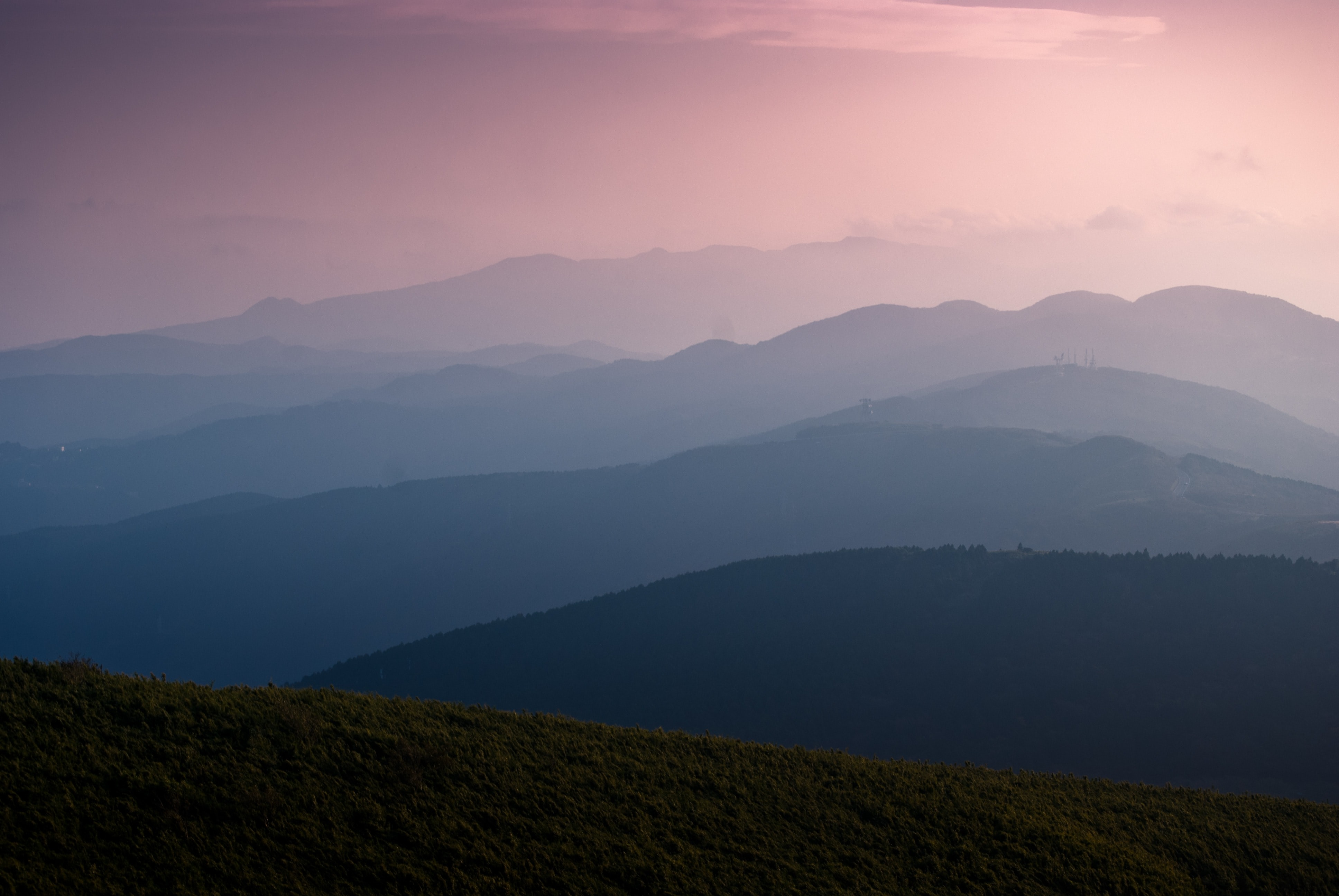 Mountains and hills glowing purple and pink during sunrise or sunset in the Izu Peninsula
