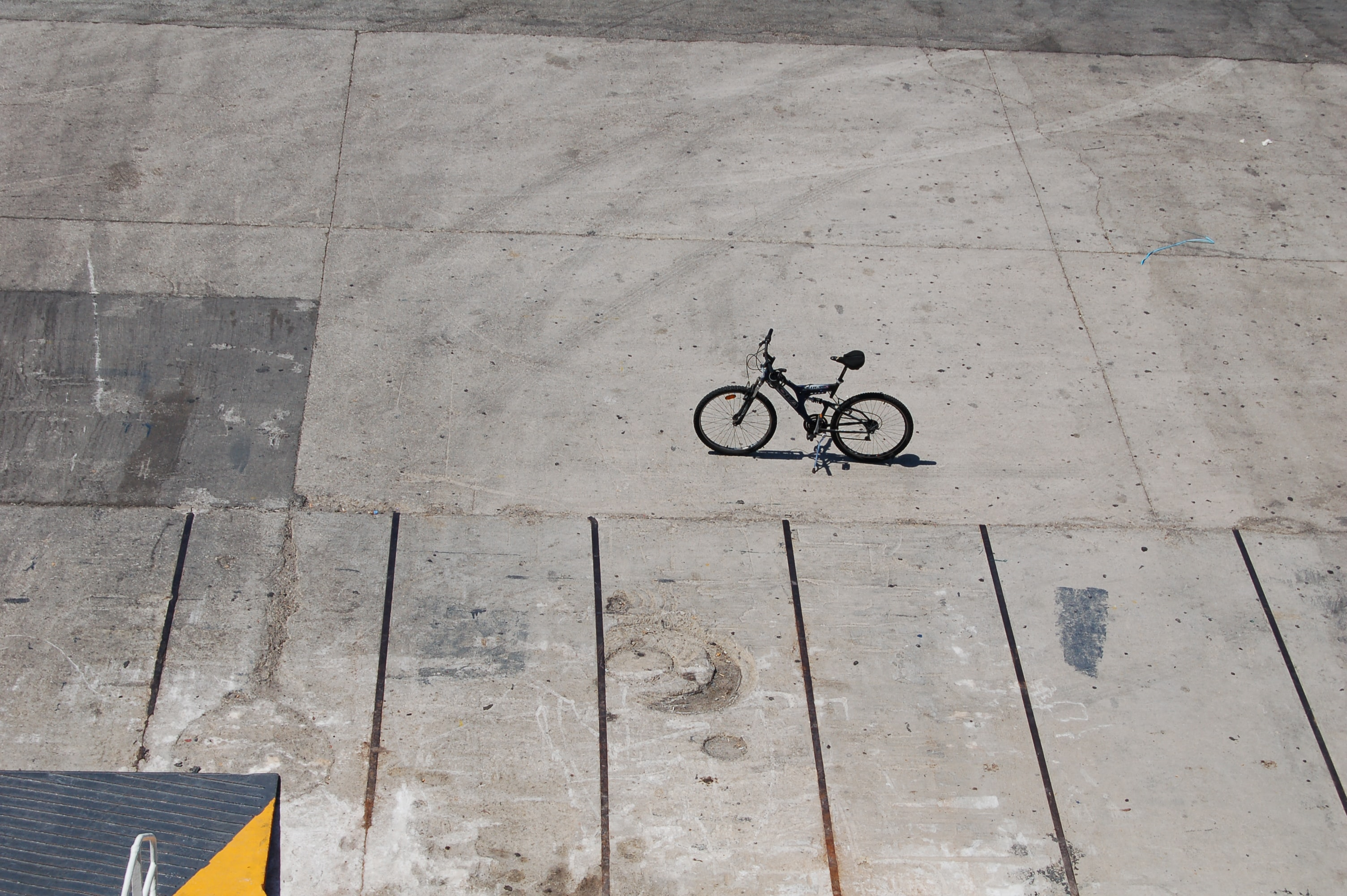 Bicycle with black frame on a textured, concrete sidewalk in Piraeus