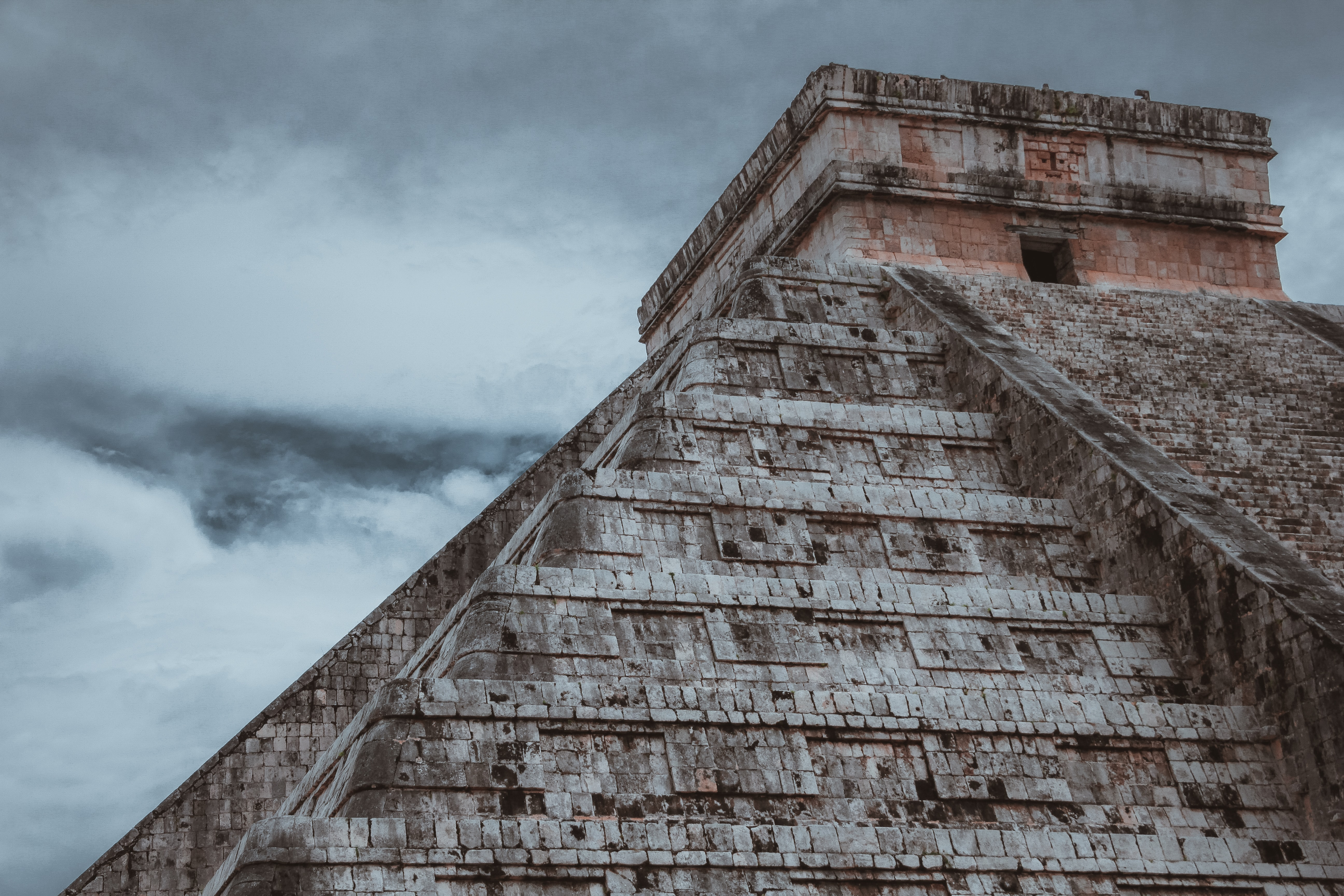 Looking up at an ancient stone pyramid under a cloudy sky in Chichén Itzá