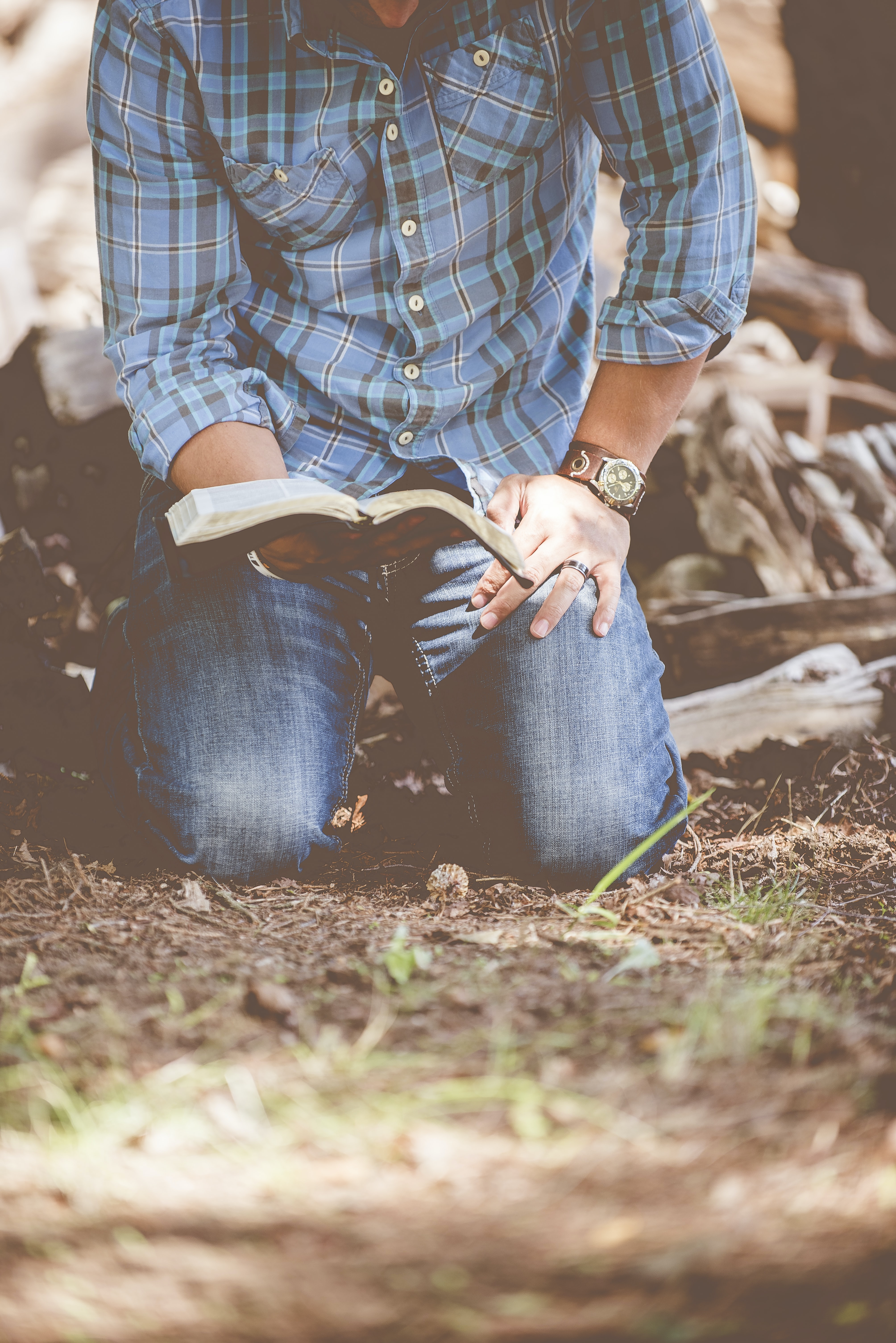 person reading book while kneeling