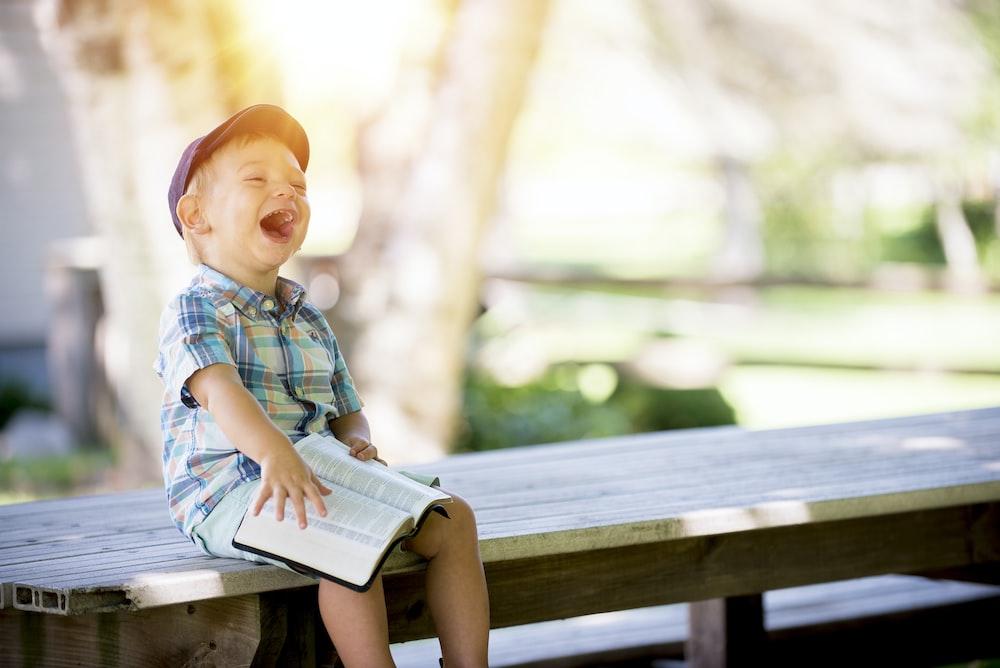 本を持ってベンチに座っている少年