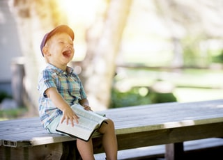 boy sitting on bench while holding a book