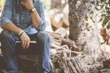 man wearing blue plaid dress shirt and blue jeans