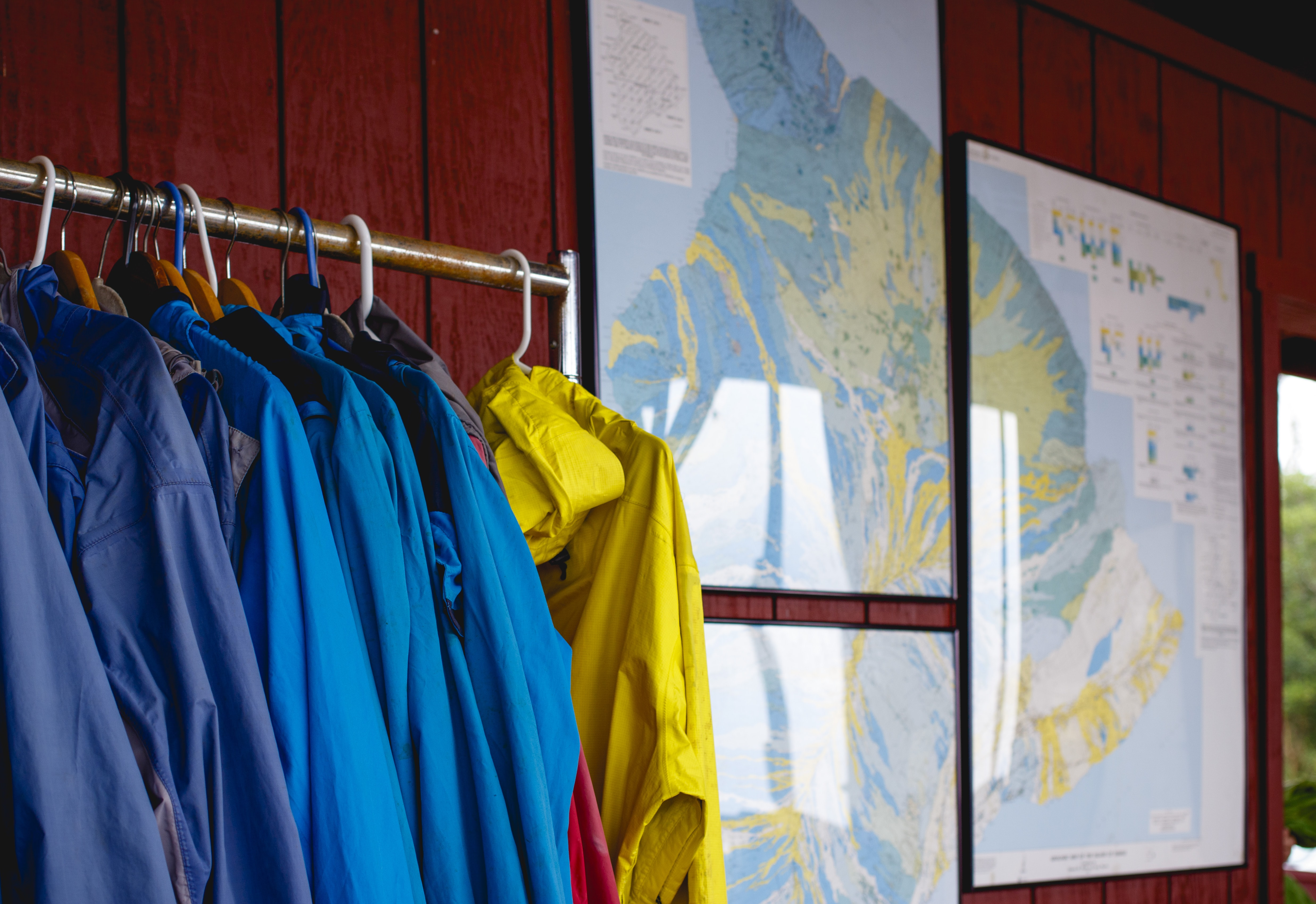 A rack of raincoats next to several framed maps hanging on a red paneled wall