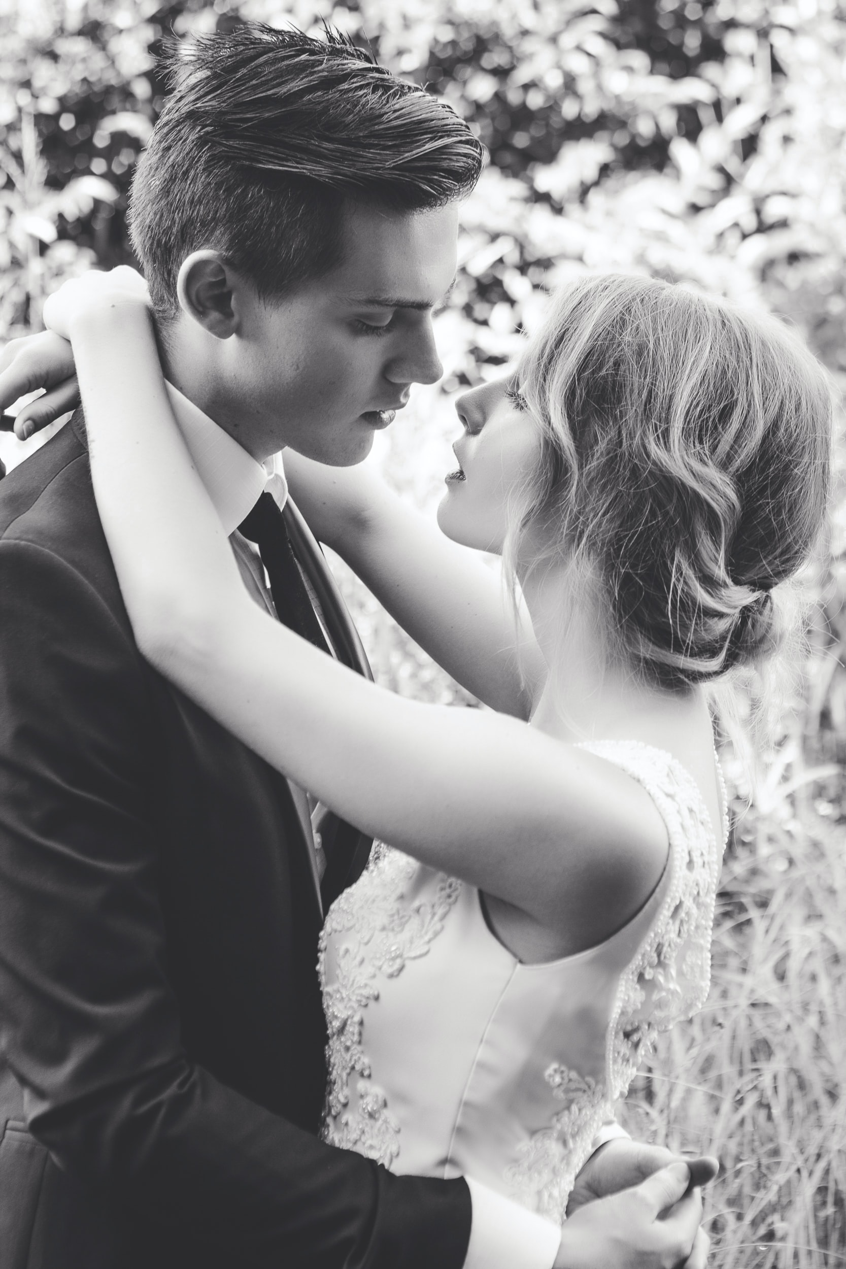 A bride and groom hugging and about to kiss.