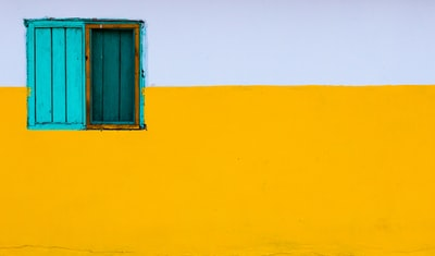 yellow and white painted wall with blue window turquoise teams background
