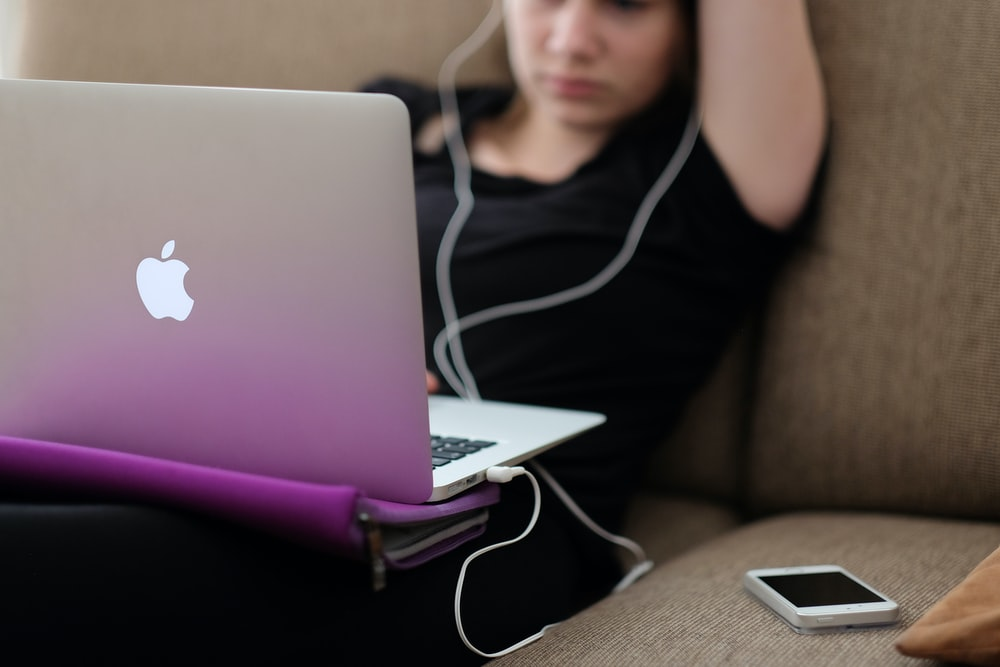woman sitting on sofa with MacBook Air