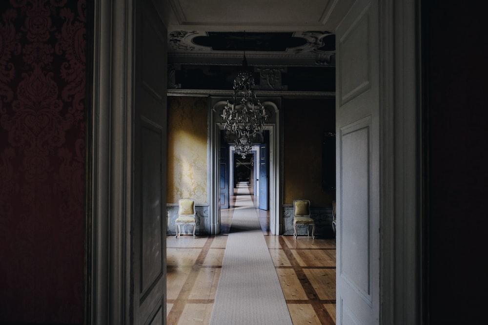 opened white wooden door near chandelier