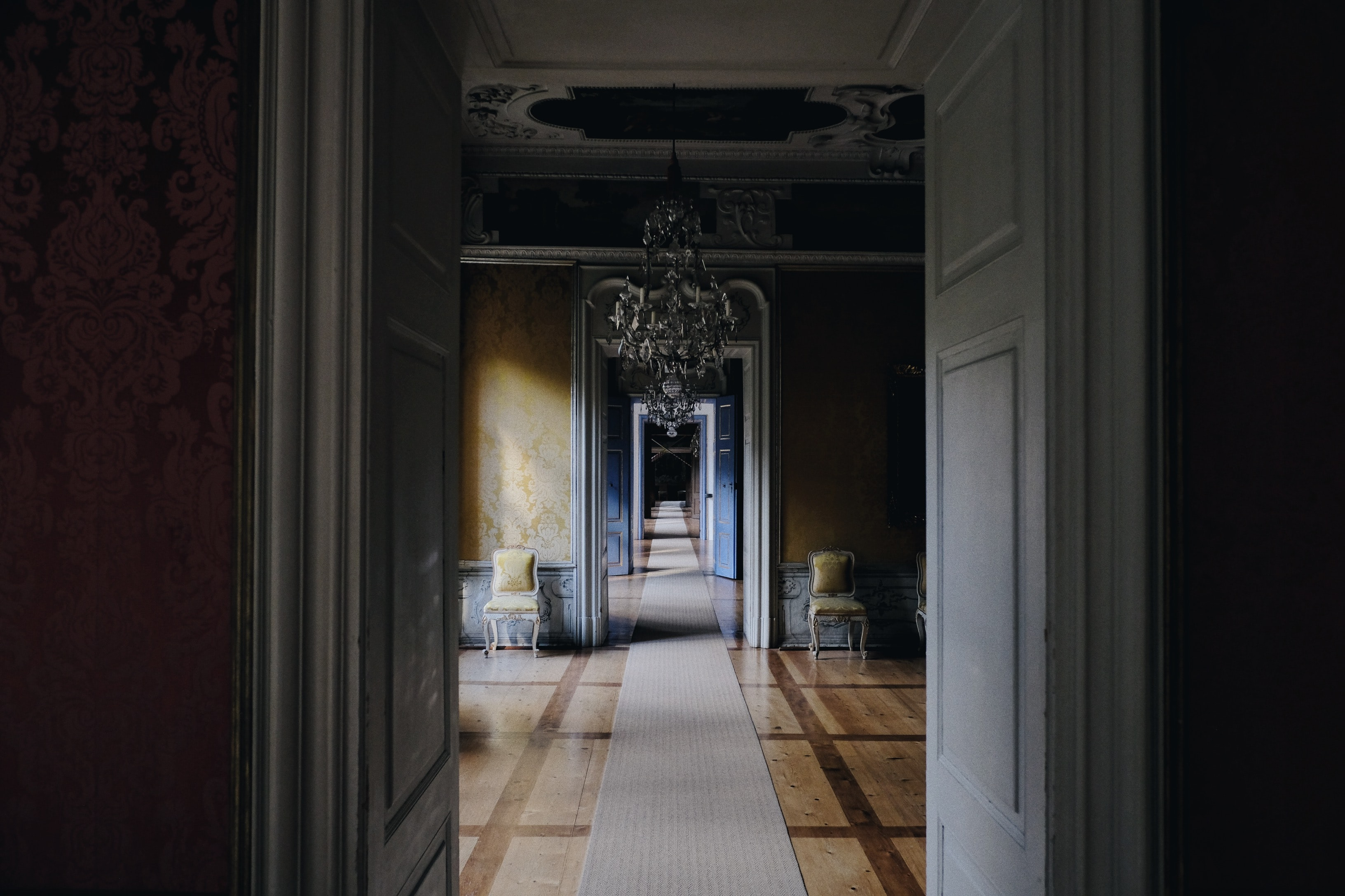 Long hallway through many rooms with a classic style and chandelier in the first room